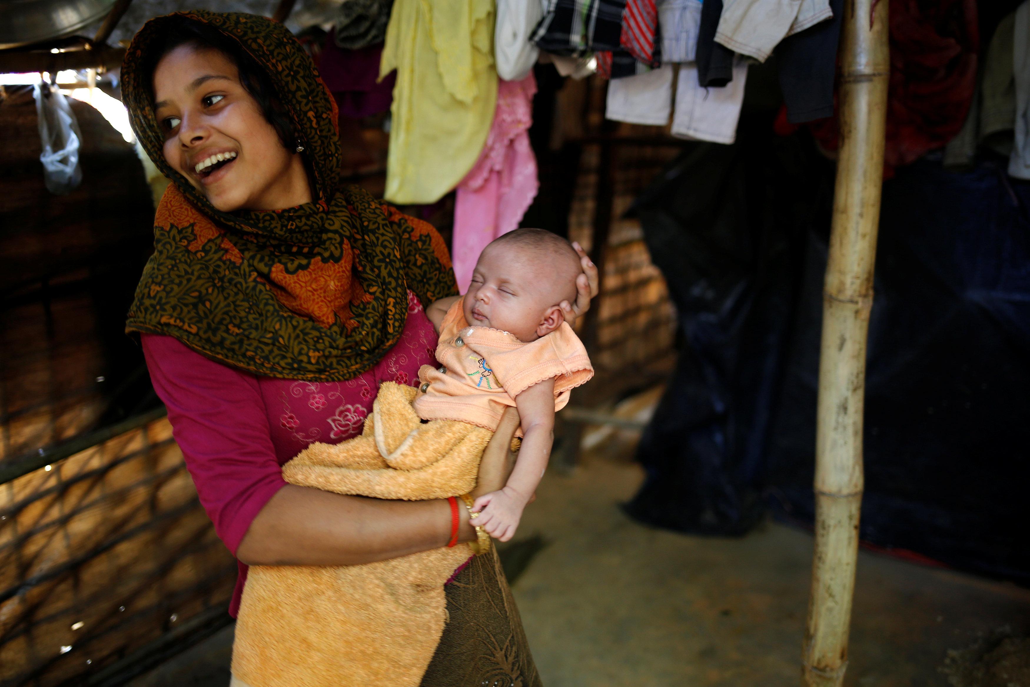سيدة من مسلمى الروهينجا تحمل طفلا