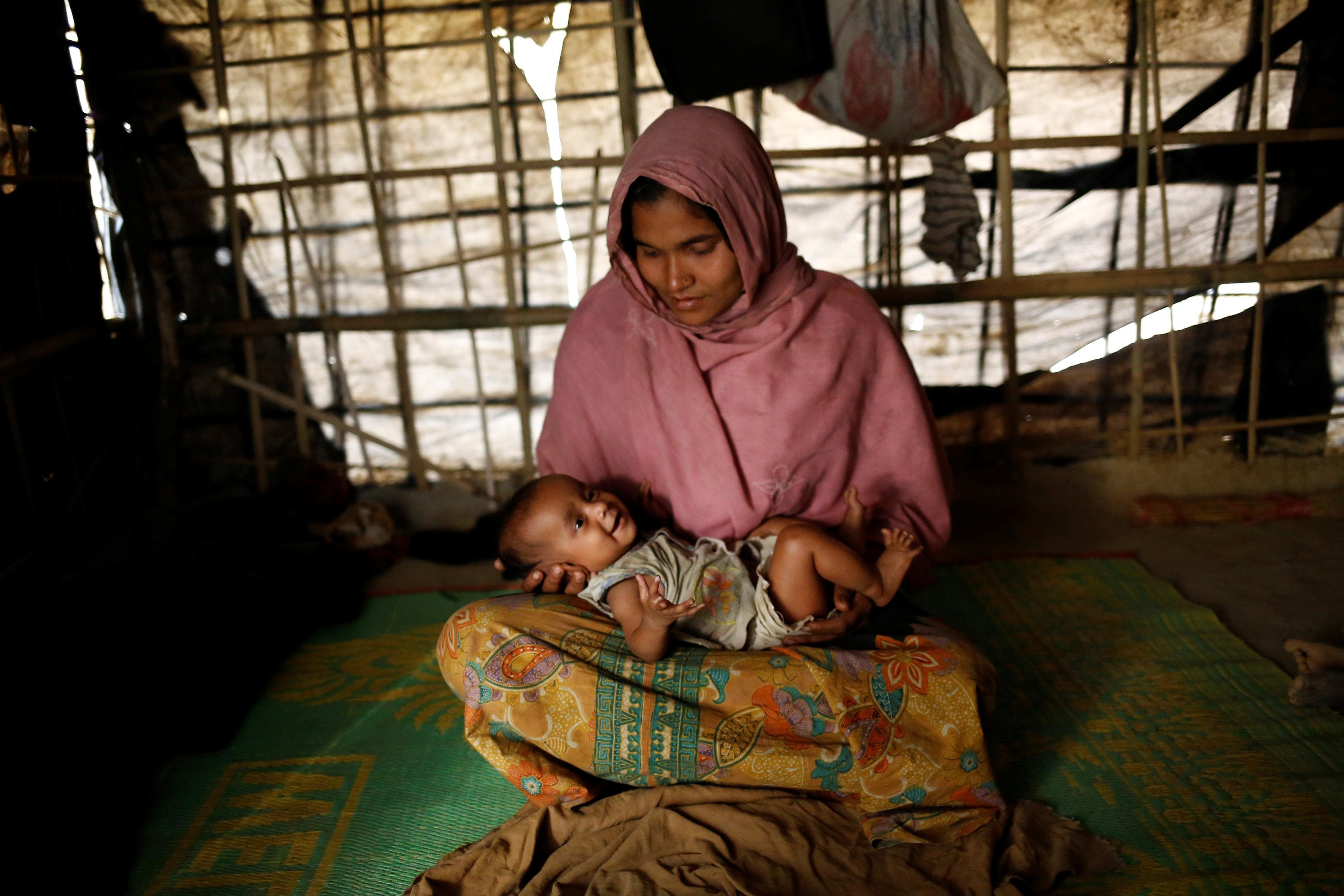 سيدة من مسلمى الروهينجا تحمل طفلها