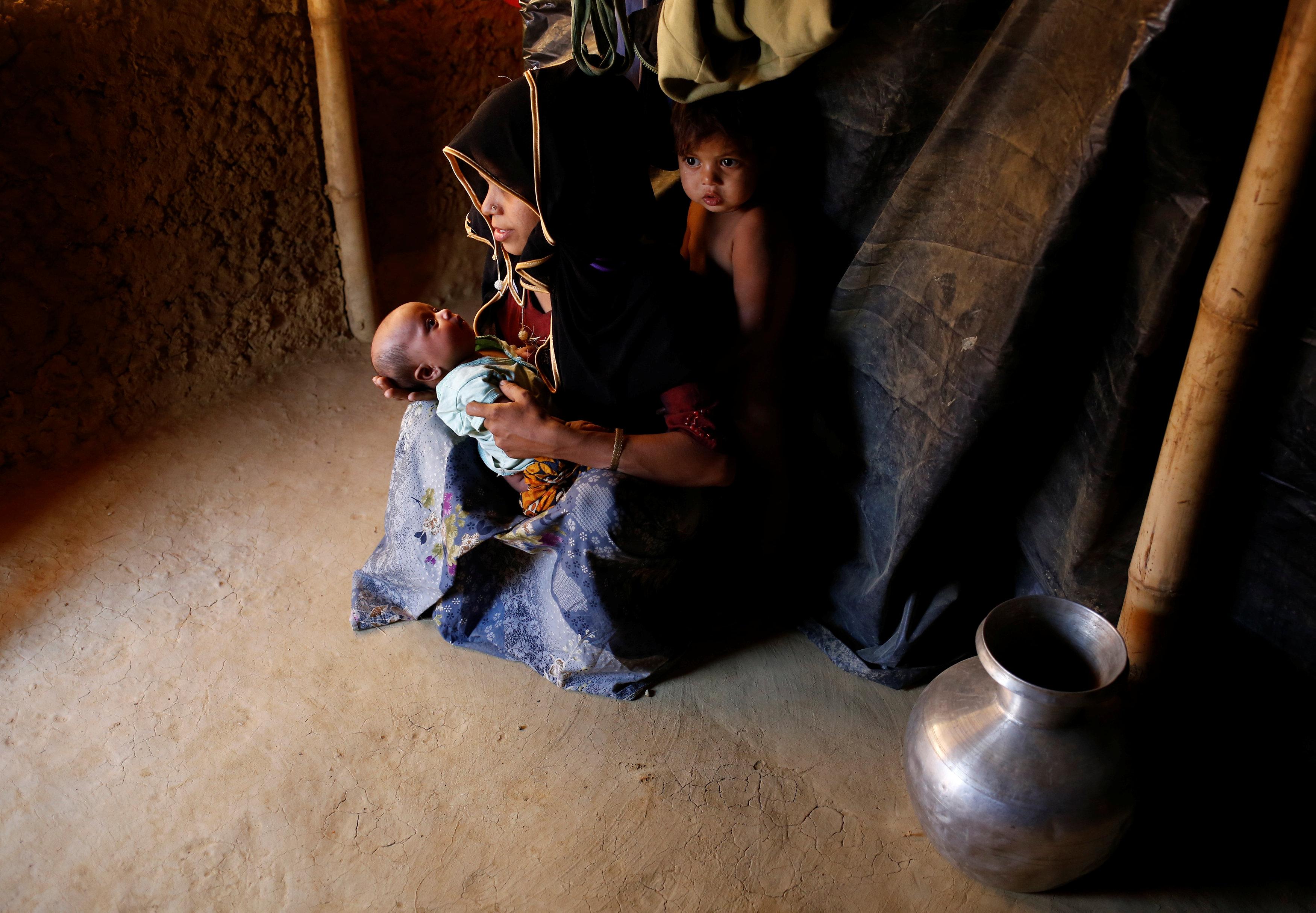 سيدة مع اطفالها داخل مخيم للاجئين