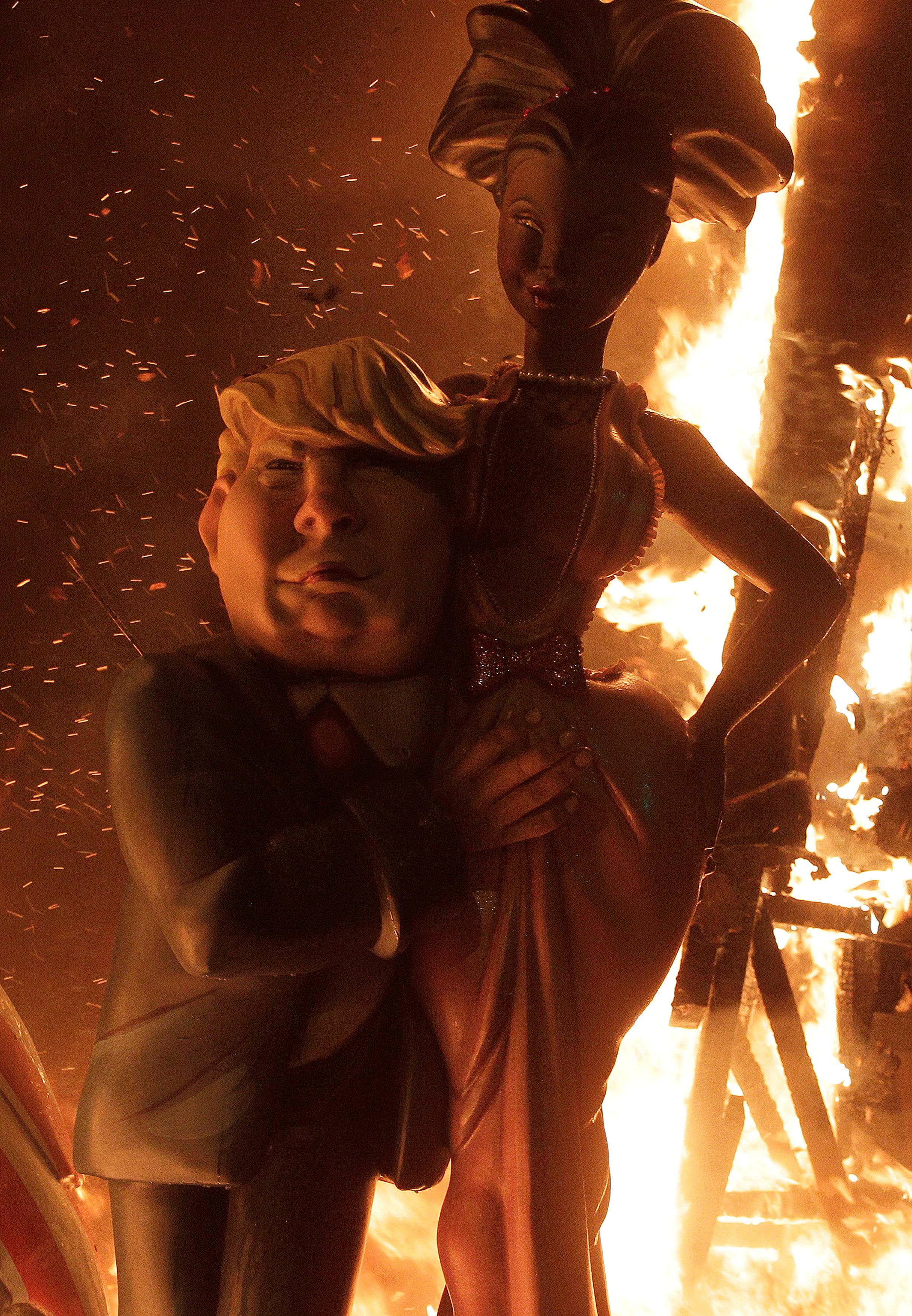 النيران تلتهم التماثيل من خلف تمثال ترامب