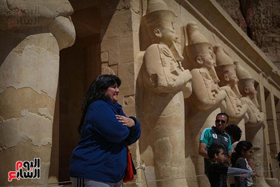 سائحة تأخذ وضع إحدى التماثيل بالمعبد