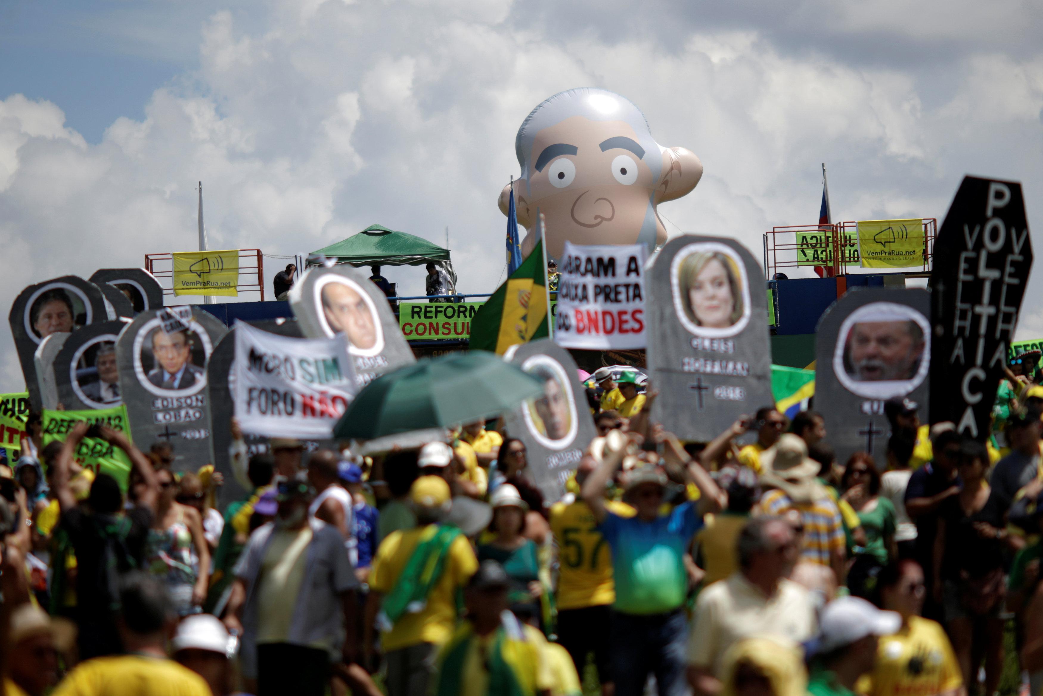 متظاهرون يحملون صورا للسياسيين البرازيليين أثناء احتجاجهم على الفساد