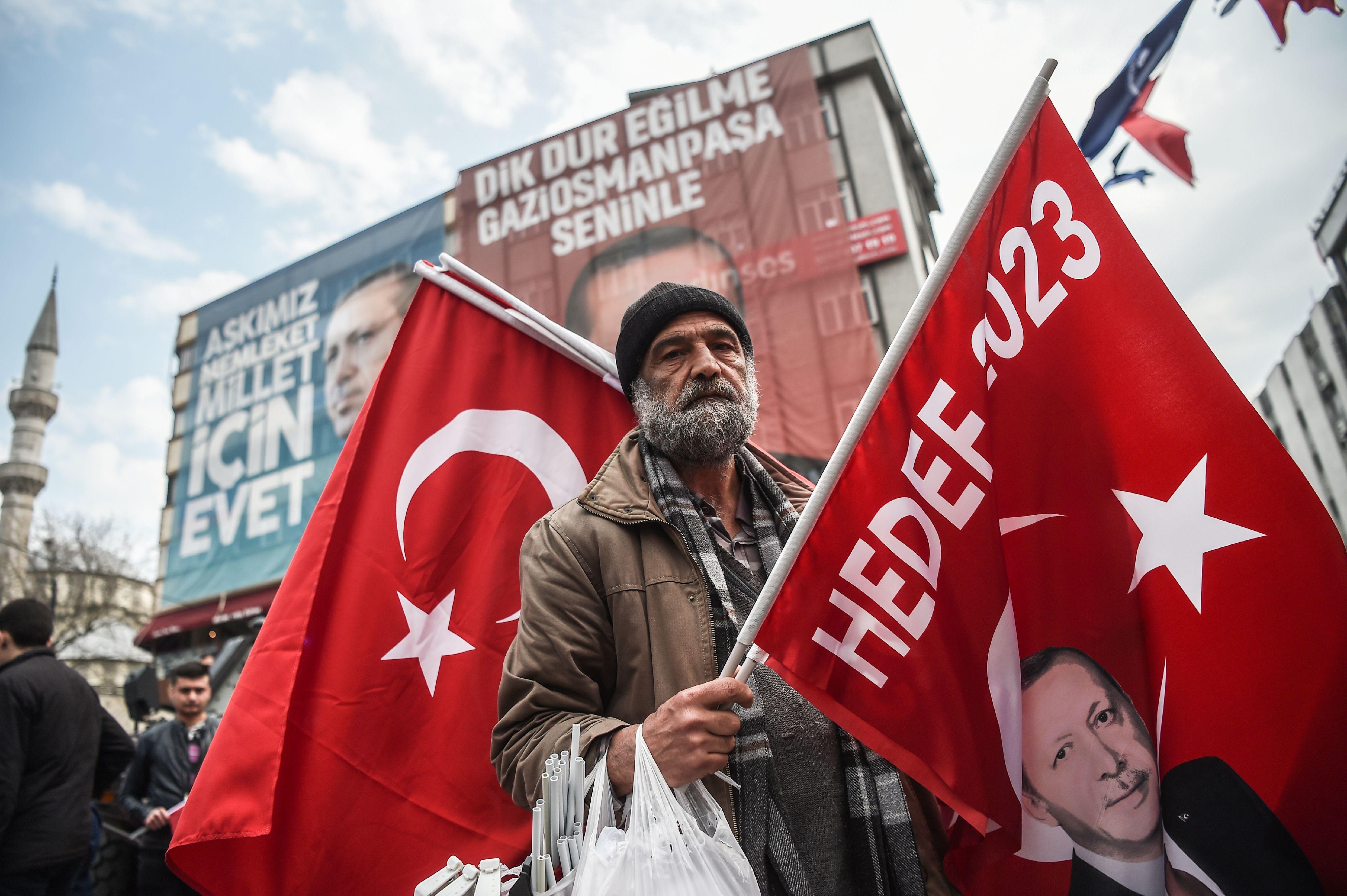رجل يحمل صور أردوغان وعلم تركيا