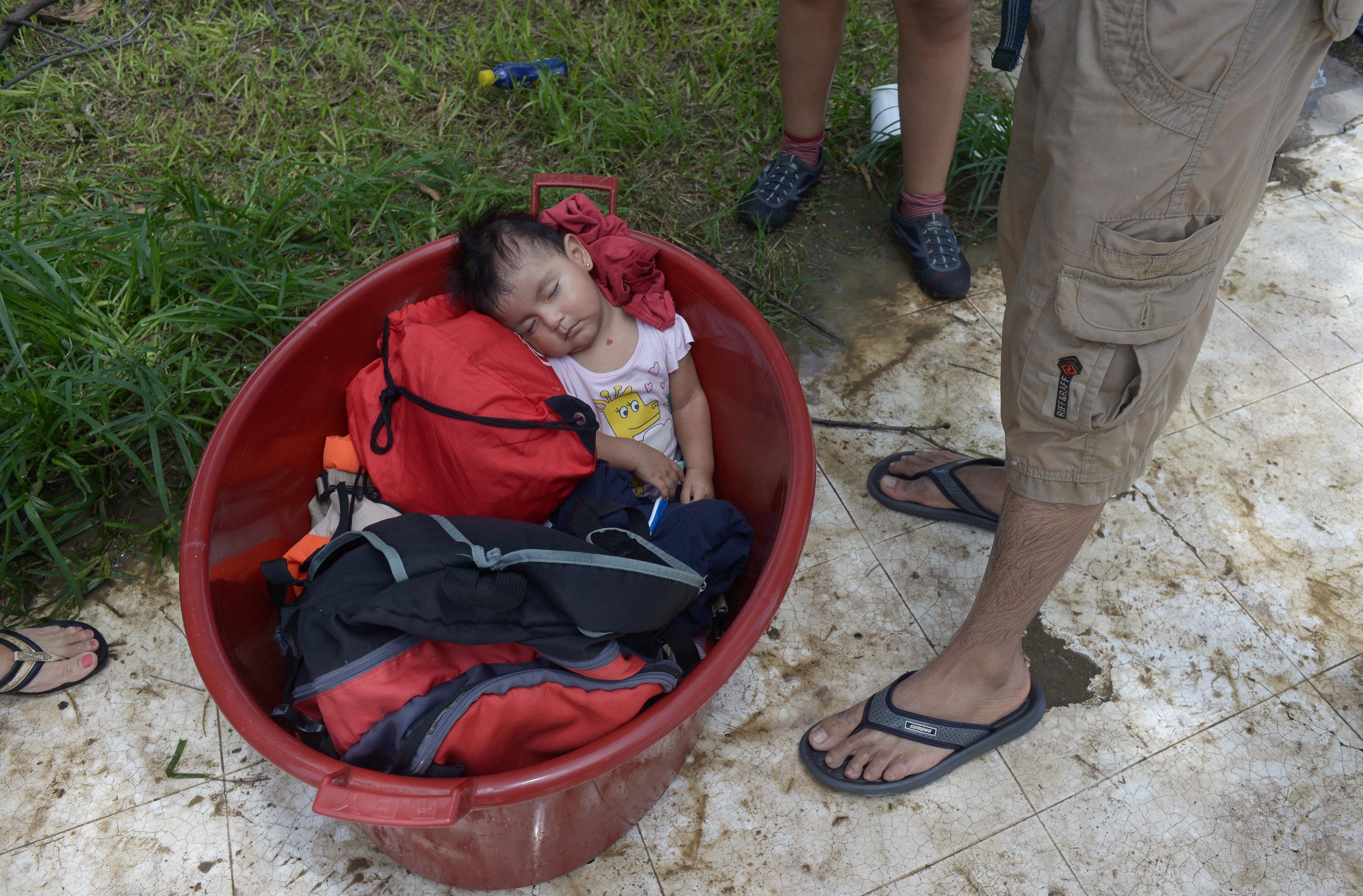 طفلة يغلبها النوم بعد عبور مياة الفيضانات