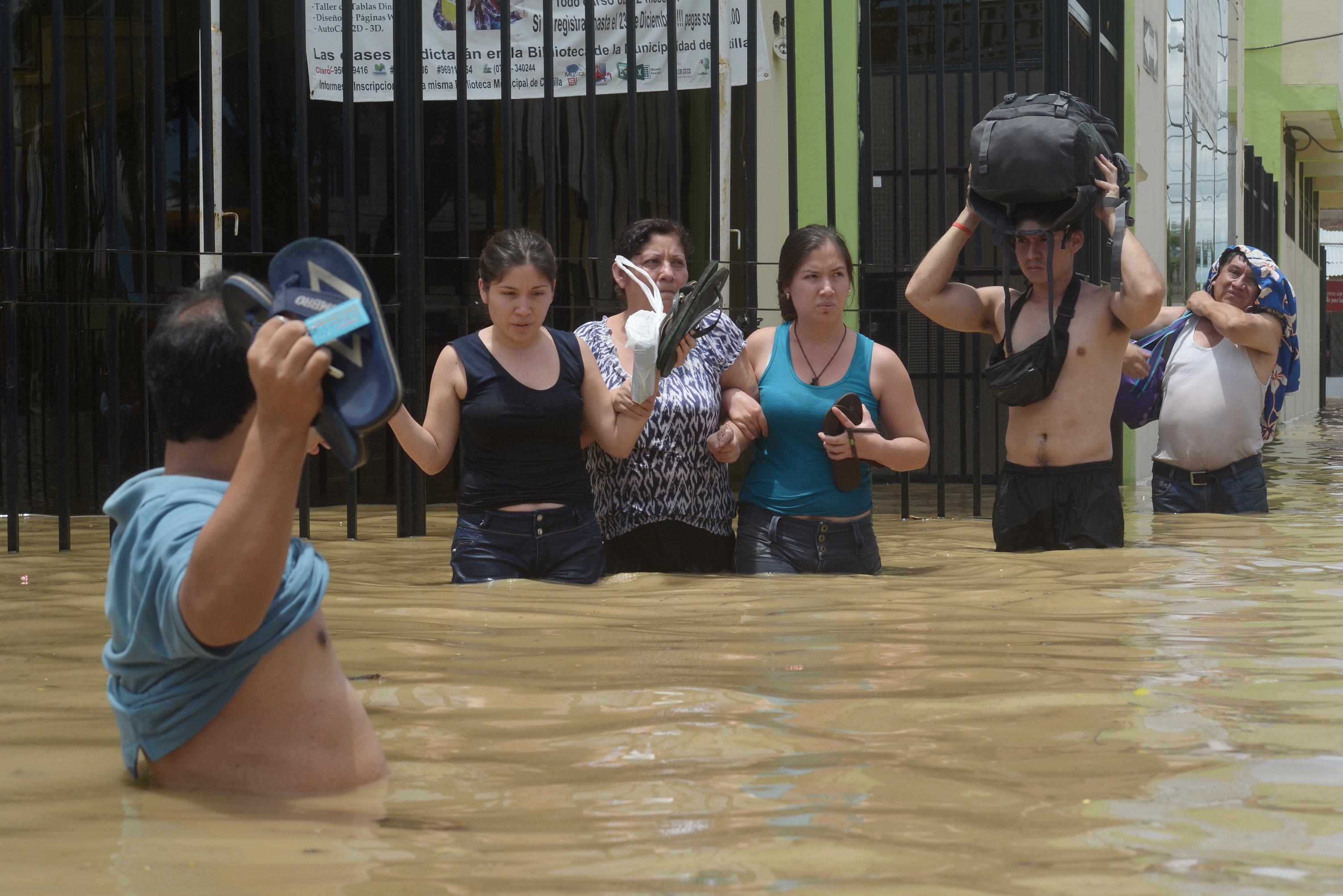 مواطنين يحملون أمتعتهم فى محاولة لعبور مياة الفيضان