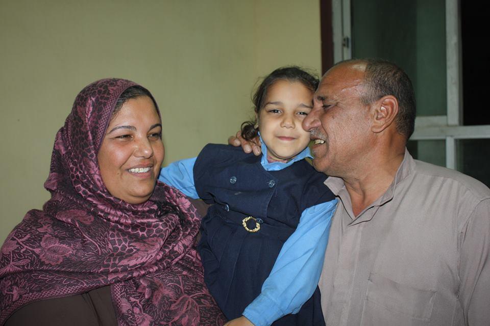 الطفلة بين والدتها ووالدها عقب عودتها