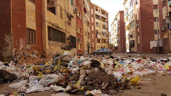تلال القمامة تحيط العمارات السكنية