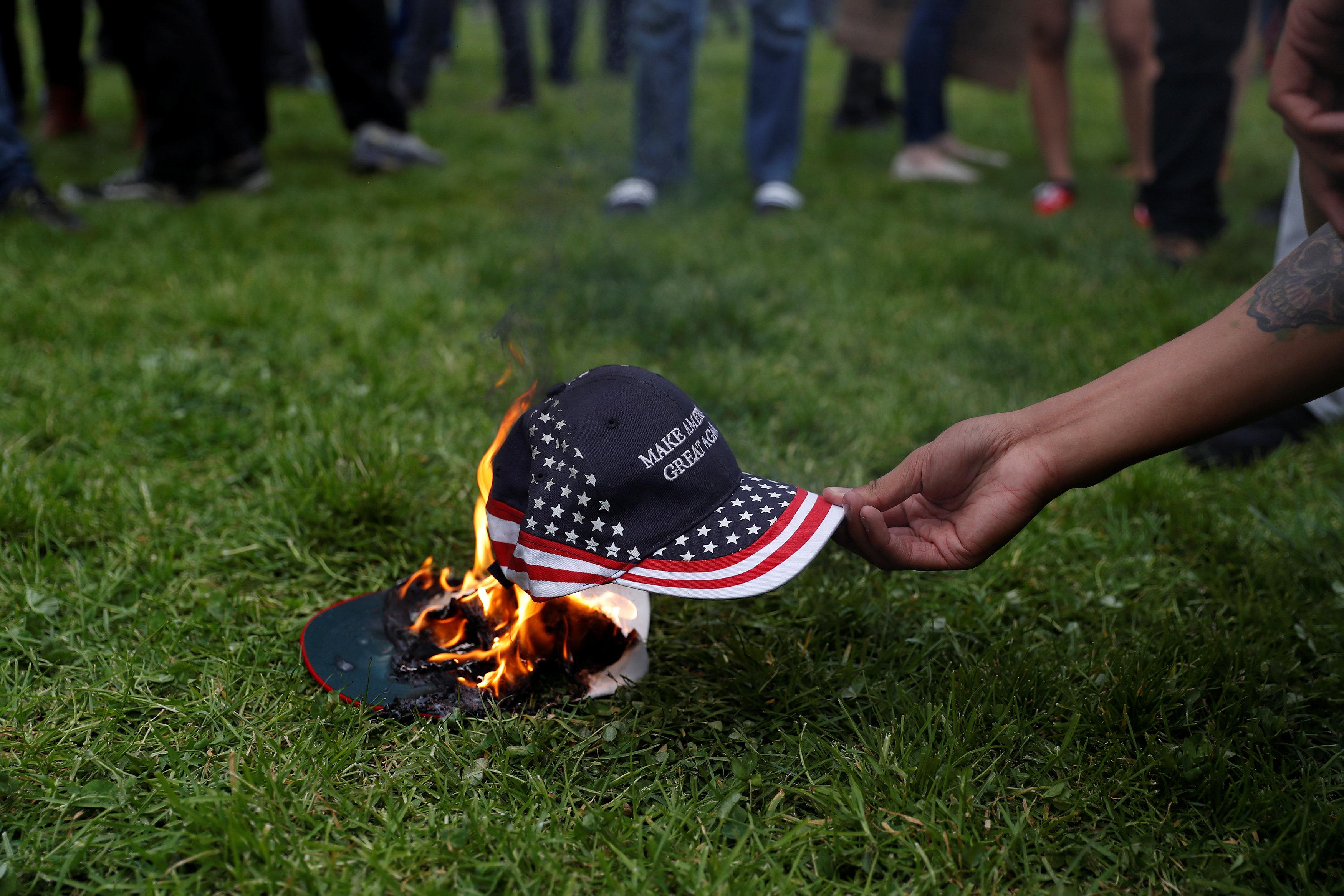أحد المحتجين على ترامب يشعل متعلقات مؤيدى ترامب