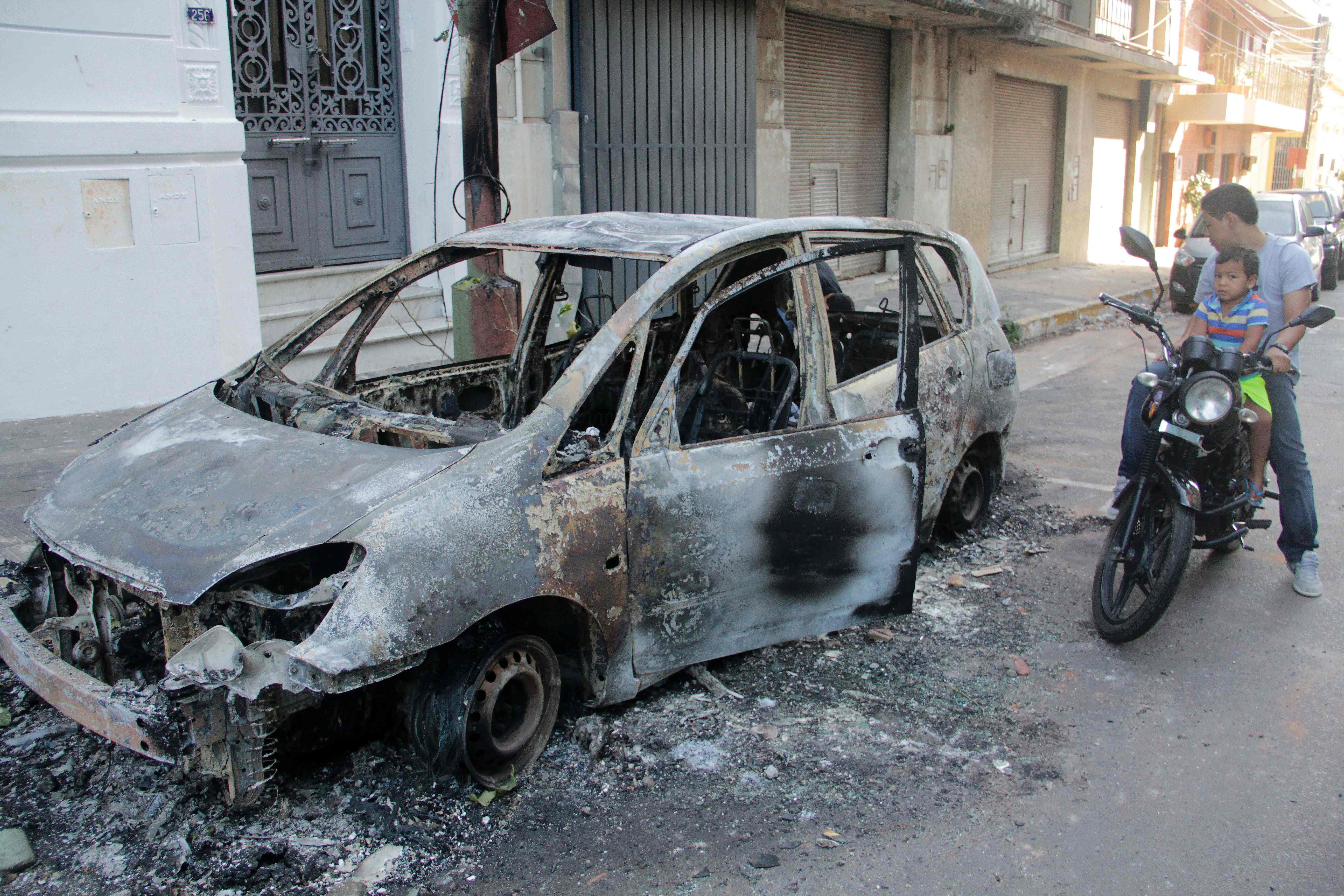 دراجة بخارية يقودها شاب قرب سيارة بعد حرقها