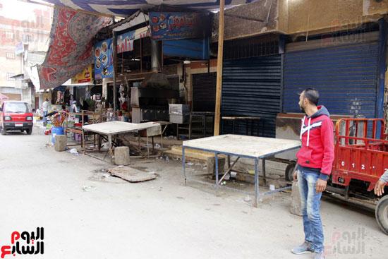 بائع يقف أمام  محله المغلق وشارع السوق بلا مشترين