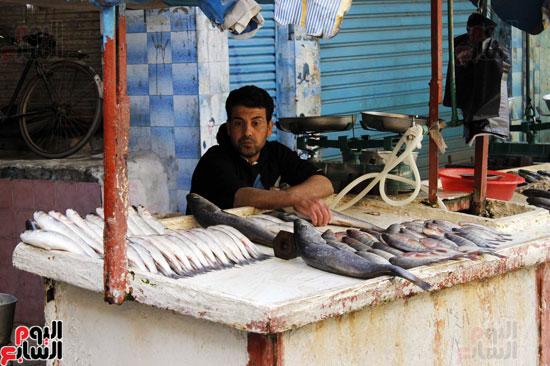 بائع  أسماك  يقف  ينتظر الزبائن