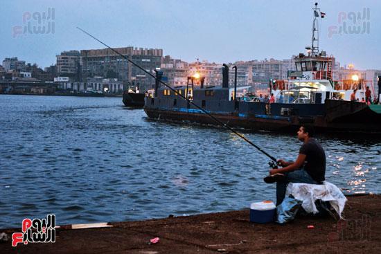 صياد هاو  يجلس  بجوار  معدية  بورسعيد