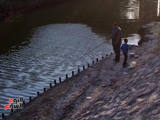 صياد  هاو  يلقي  بشباكه  في  مفيض  بحيرة التمساح
