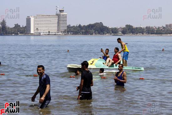 شباب يقفون علي الشاطئ  وفي الخلفية  تظهر  سفينة عابرة لقناة السويس