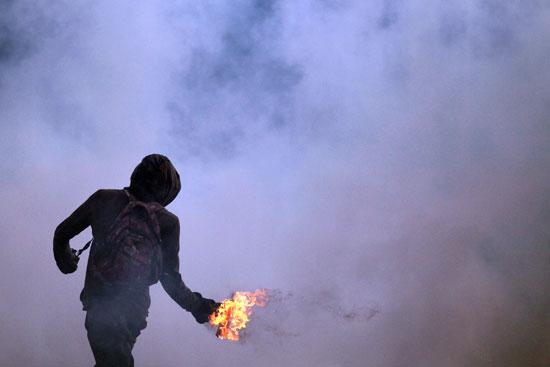 محتج يلقى زجاجة مولوتوف على قوات الأمن