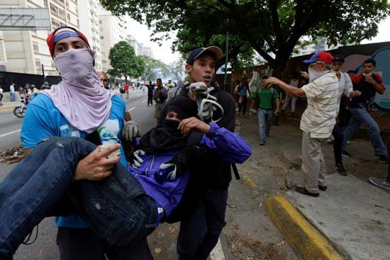 أحد المحتجين يحمل مصابا جراء الاشتباكات