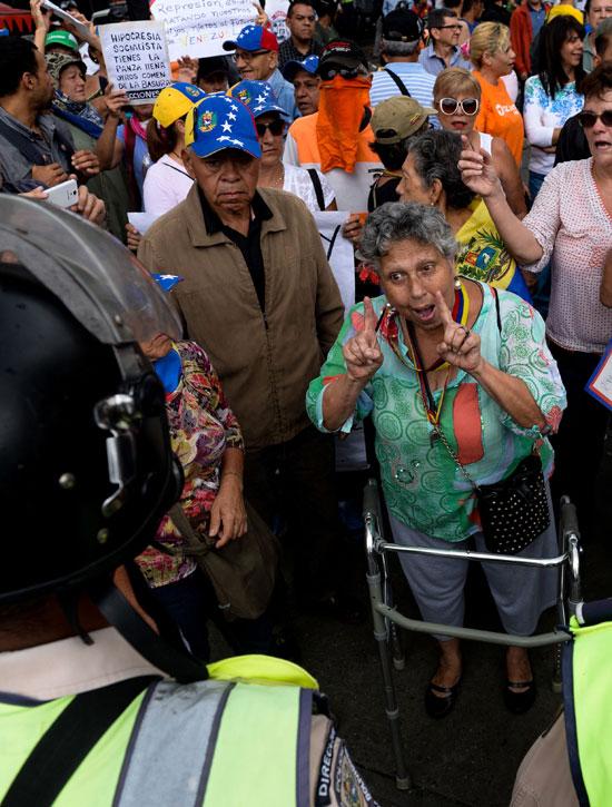 سيدة مسنه تقف وسط المحتجين