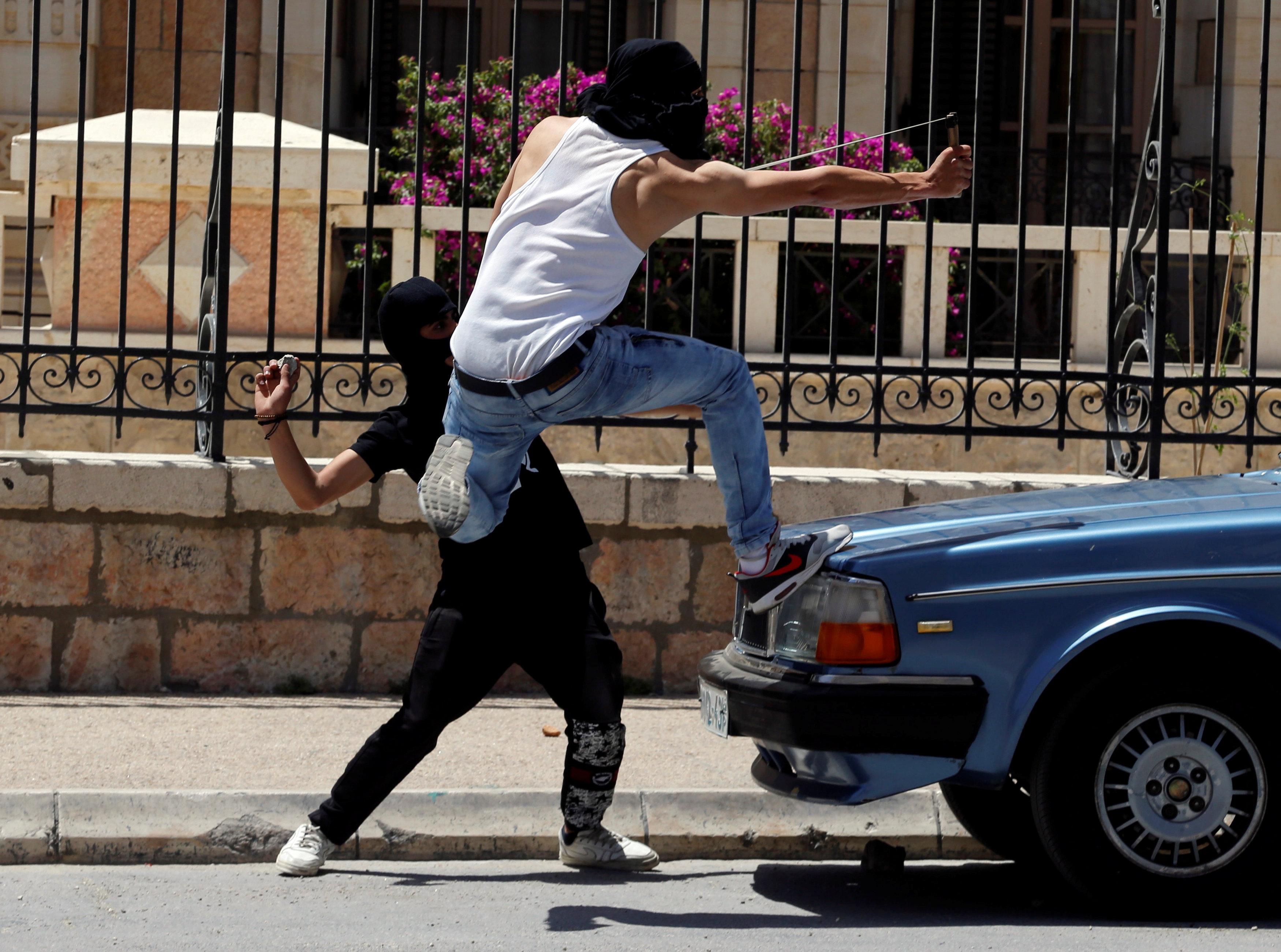 شاب يقذف الطوب على قوات الاحتلال باستخدام النبال