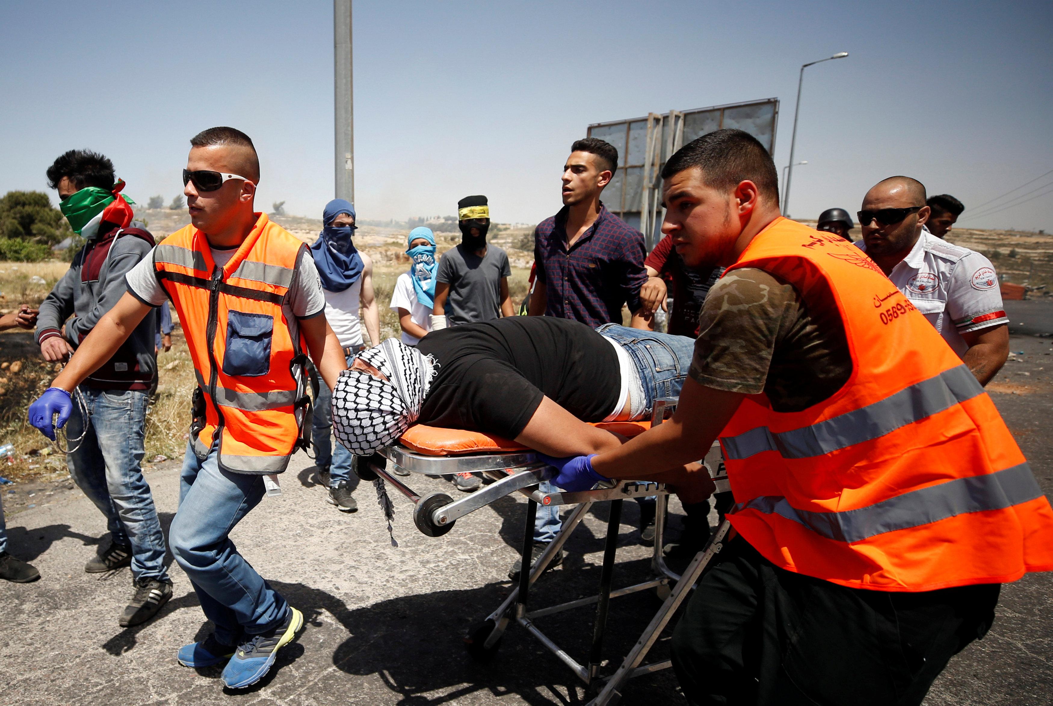 رجال الإسعاف ينقلون مصاب فى الاشتباكات