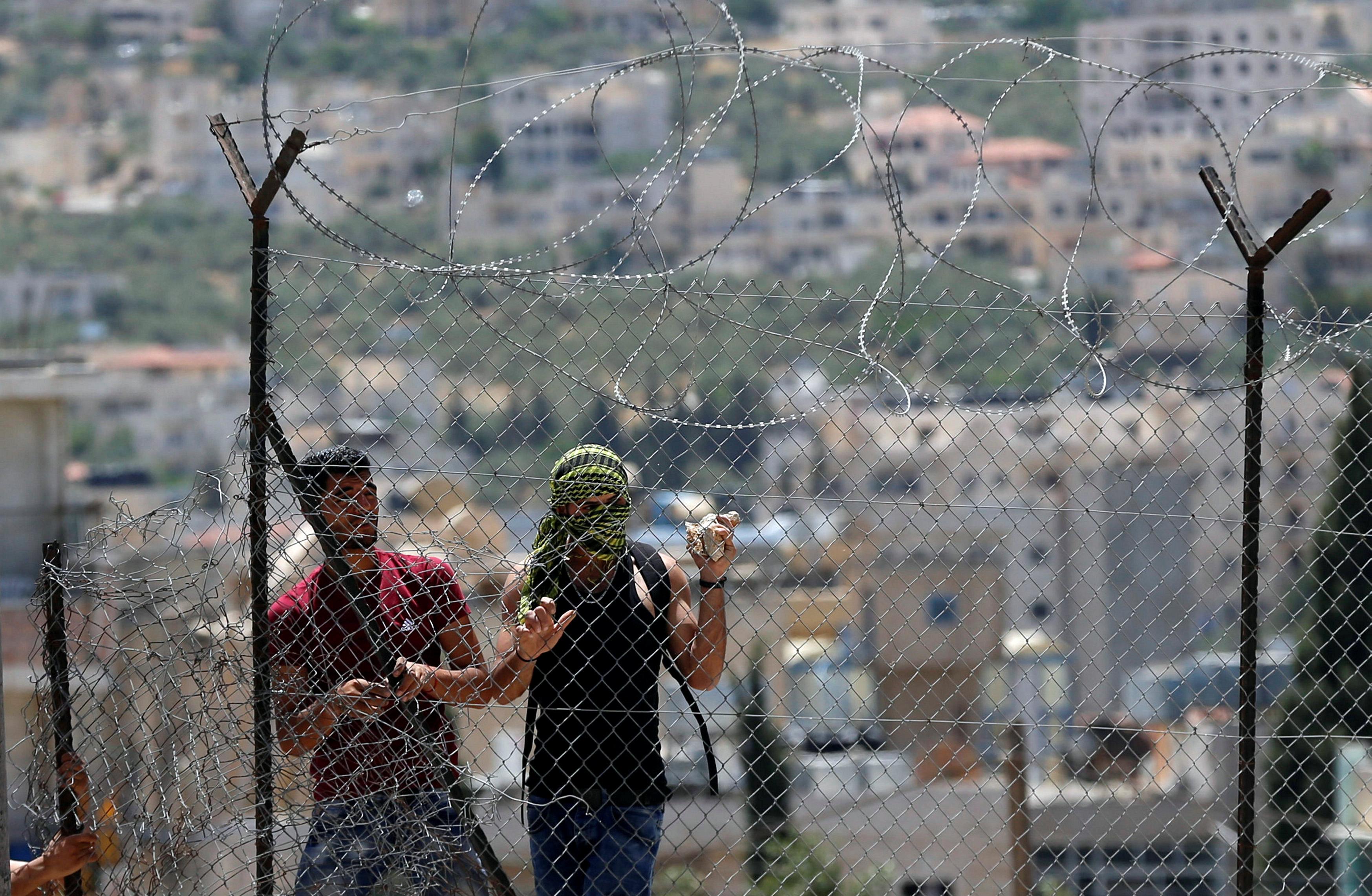 شباب خلف السياج الحديدى خلال مواجهة قوات الاحتلال