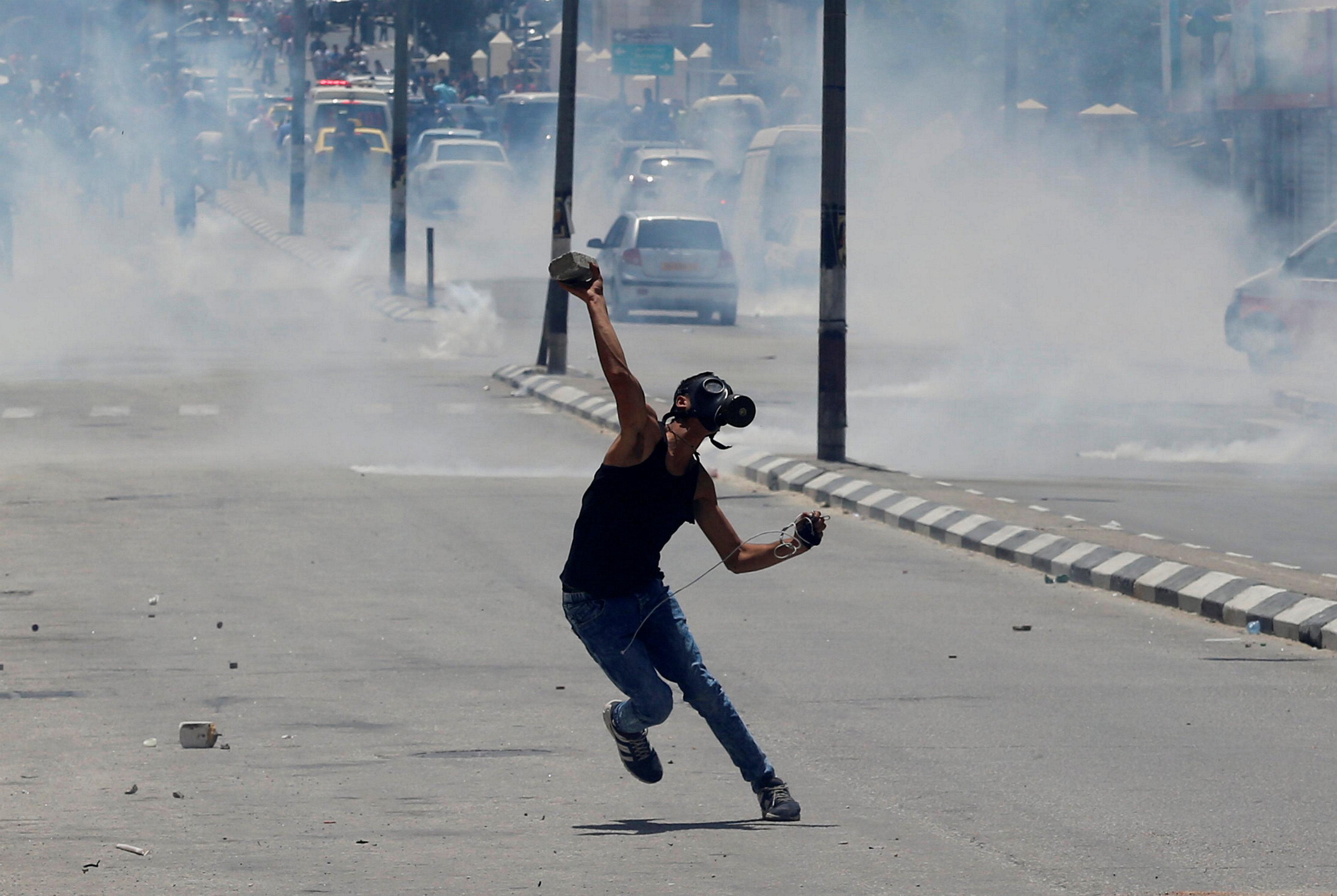 شاب يرتدى ماسك لحمايته من الغاز خلال الاشتباكات