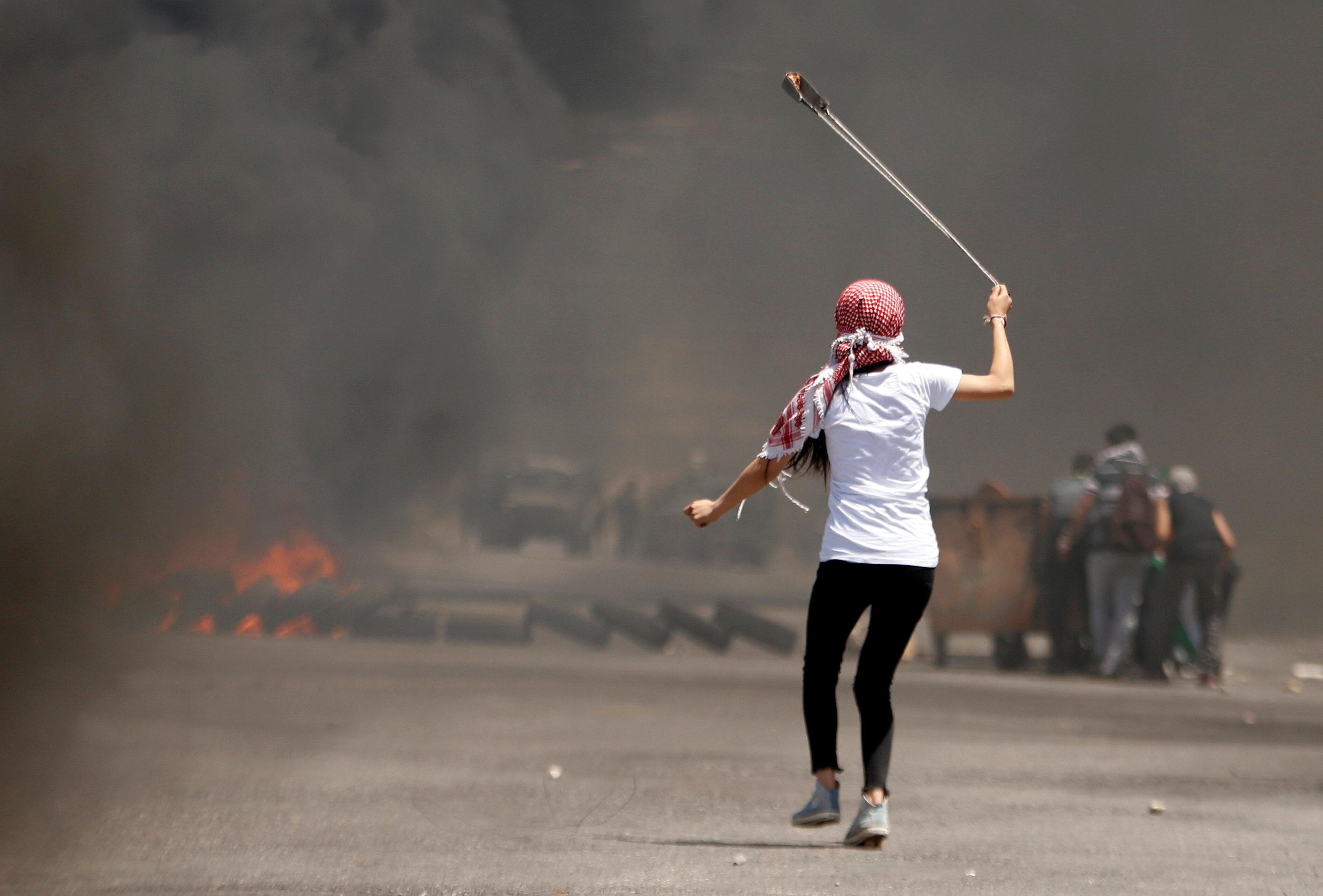 فتاة تلقى الحجارة على قوات الاحتلال
