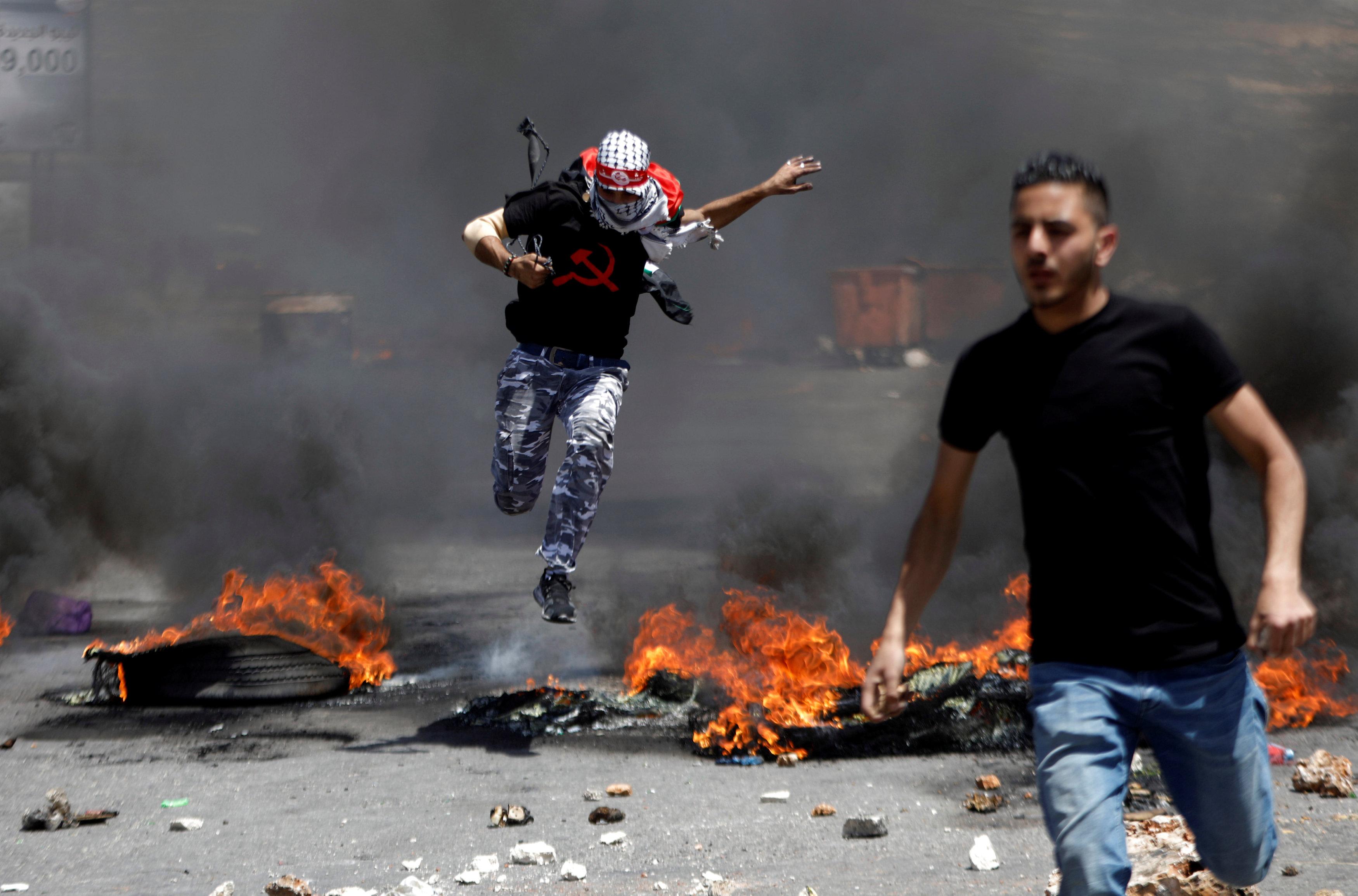 شاب يقفز أعلى النار خلال مواجهات مع قوات الاحتلال