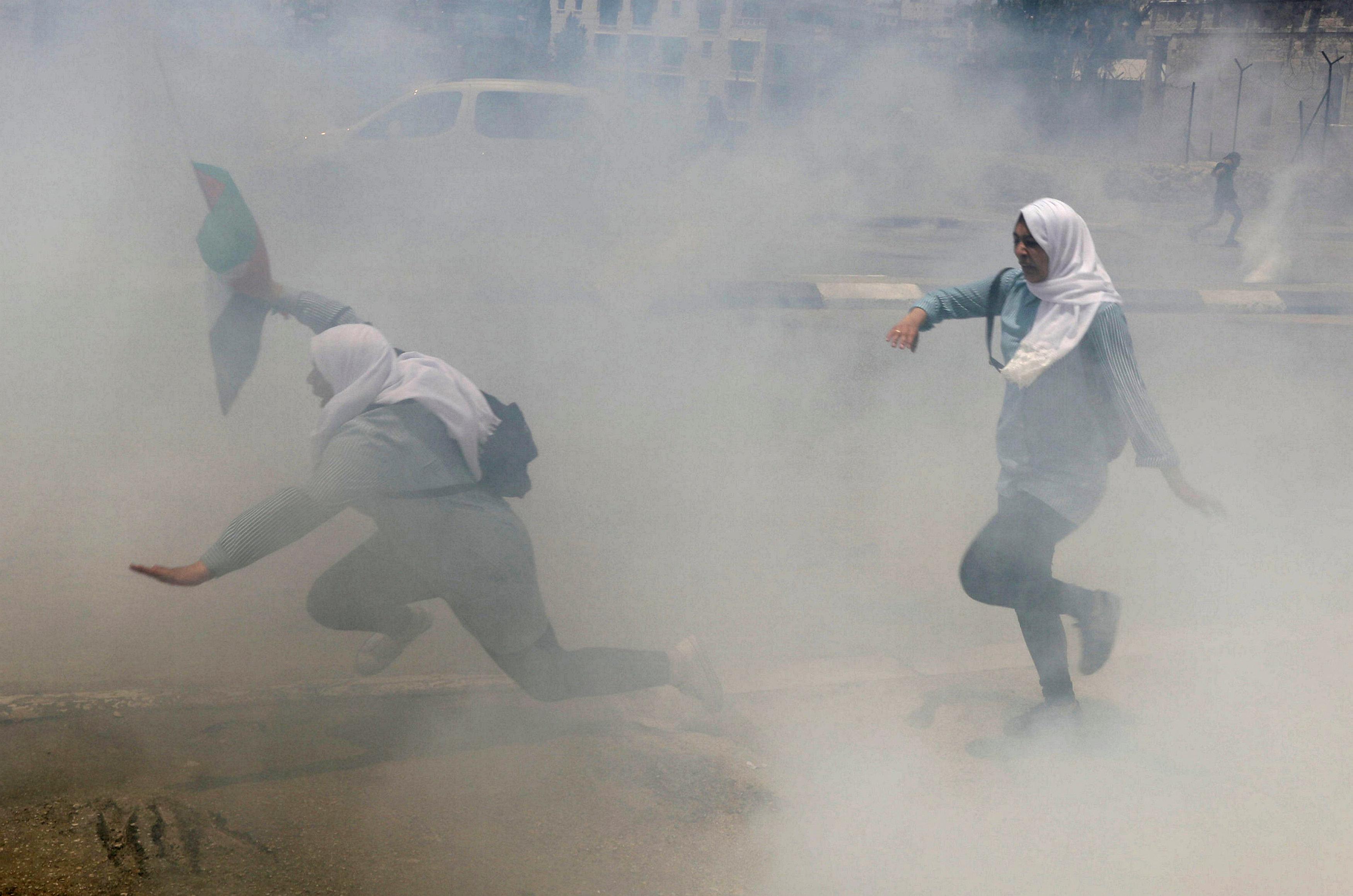 طالبات فلسطينيات يهربن من دخان الغاز المسيل للدموع