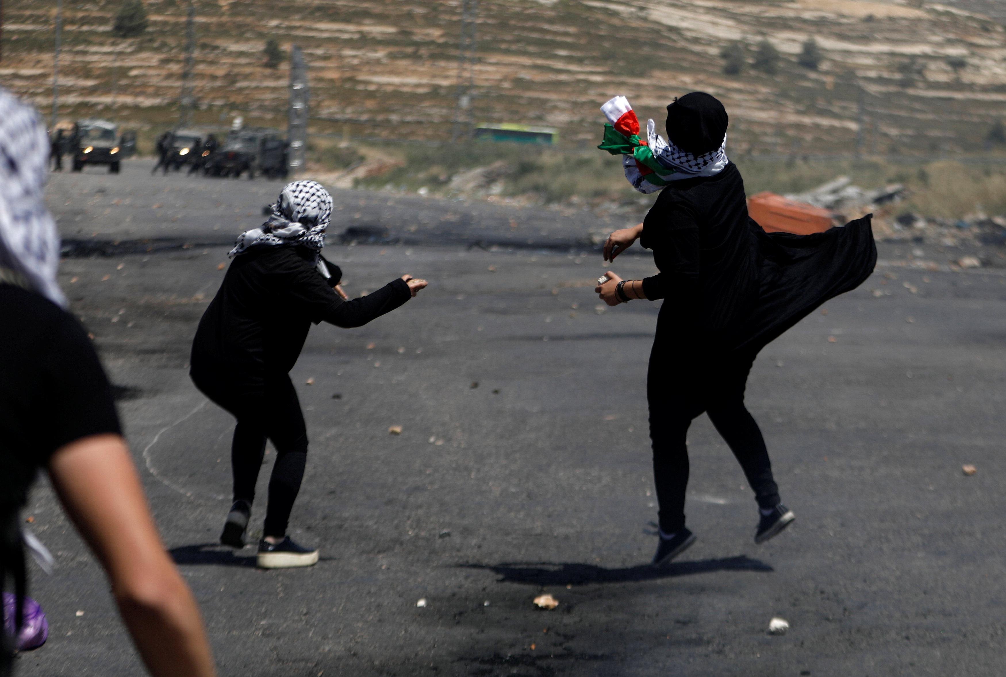 فتيات يلقين الحجارة باتجاه قوات الاحتلال الاسرائيلى