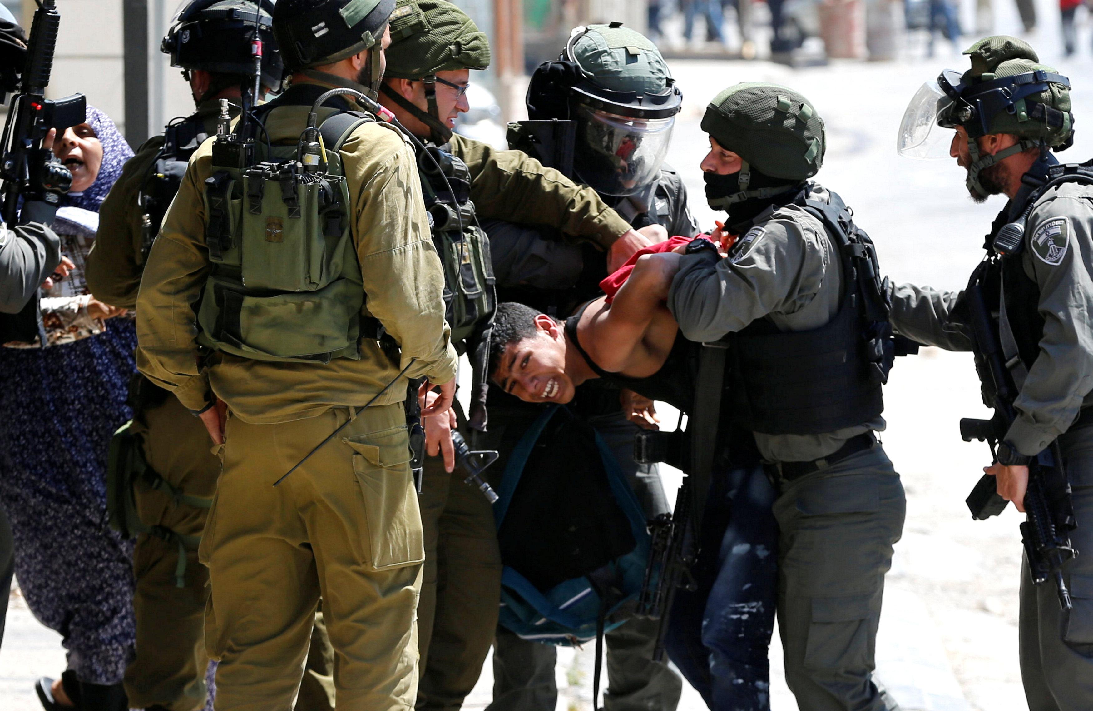 أفراد قوات الاحتلال يتجمعون حول شاب فلسطينى فور اعتقاله