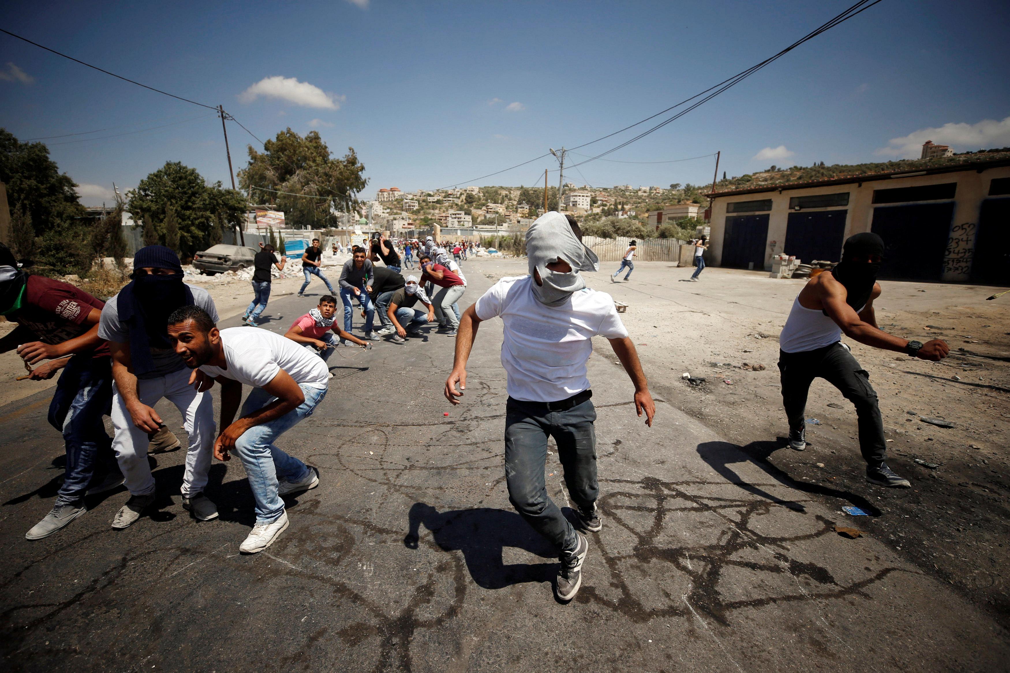 فلسطينيون يواجهون رصاص قوات الاحتلال بالحجارة