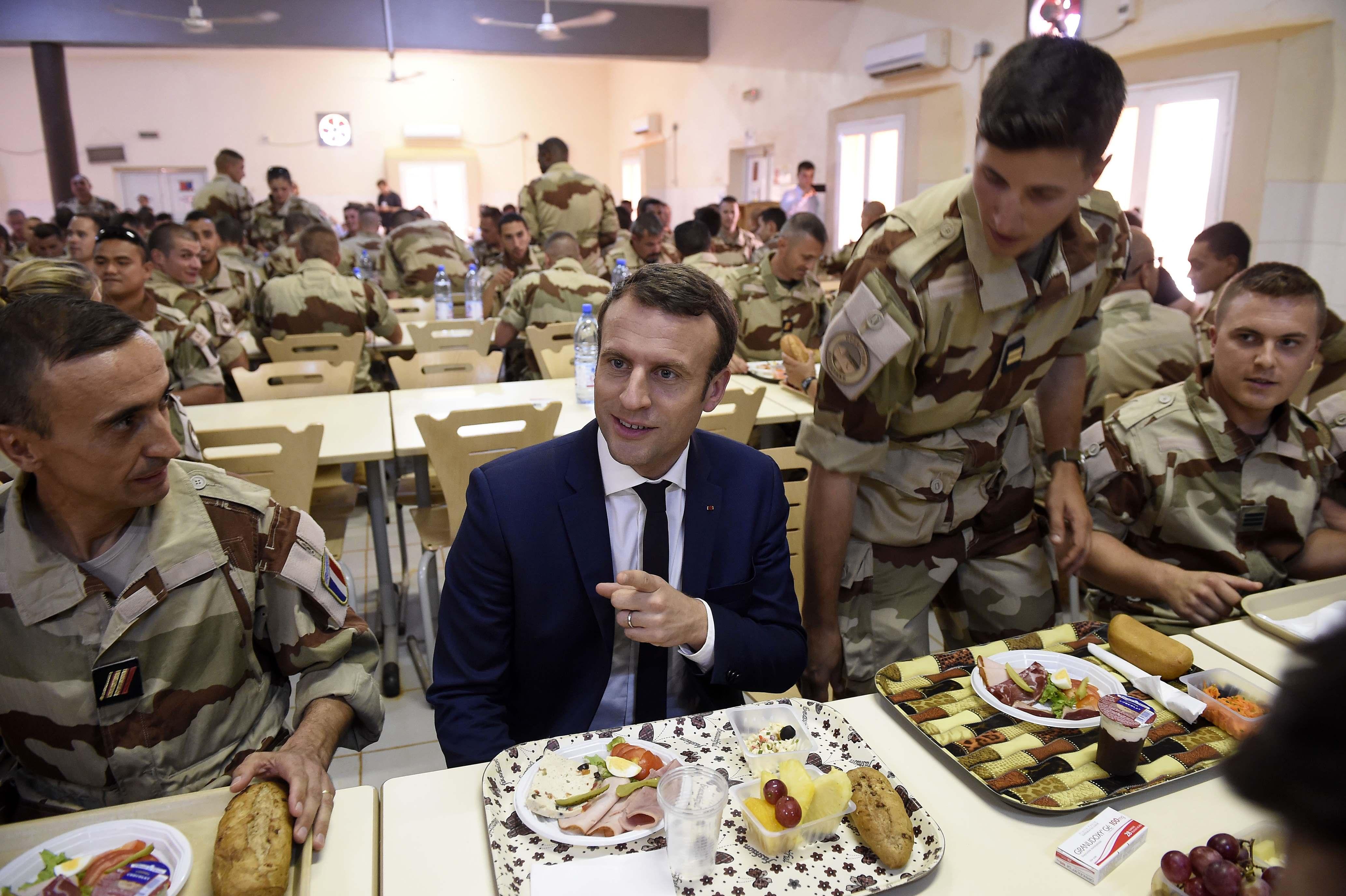 ماكرون يتحدث أثناء  تناول الطعام مع القوات الفرنسية