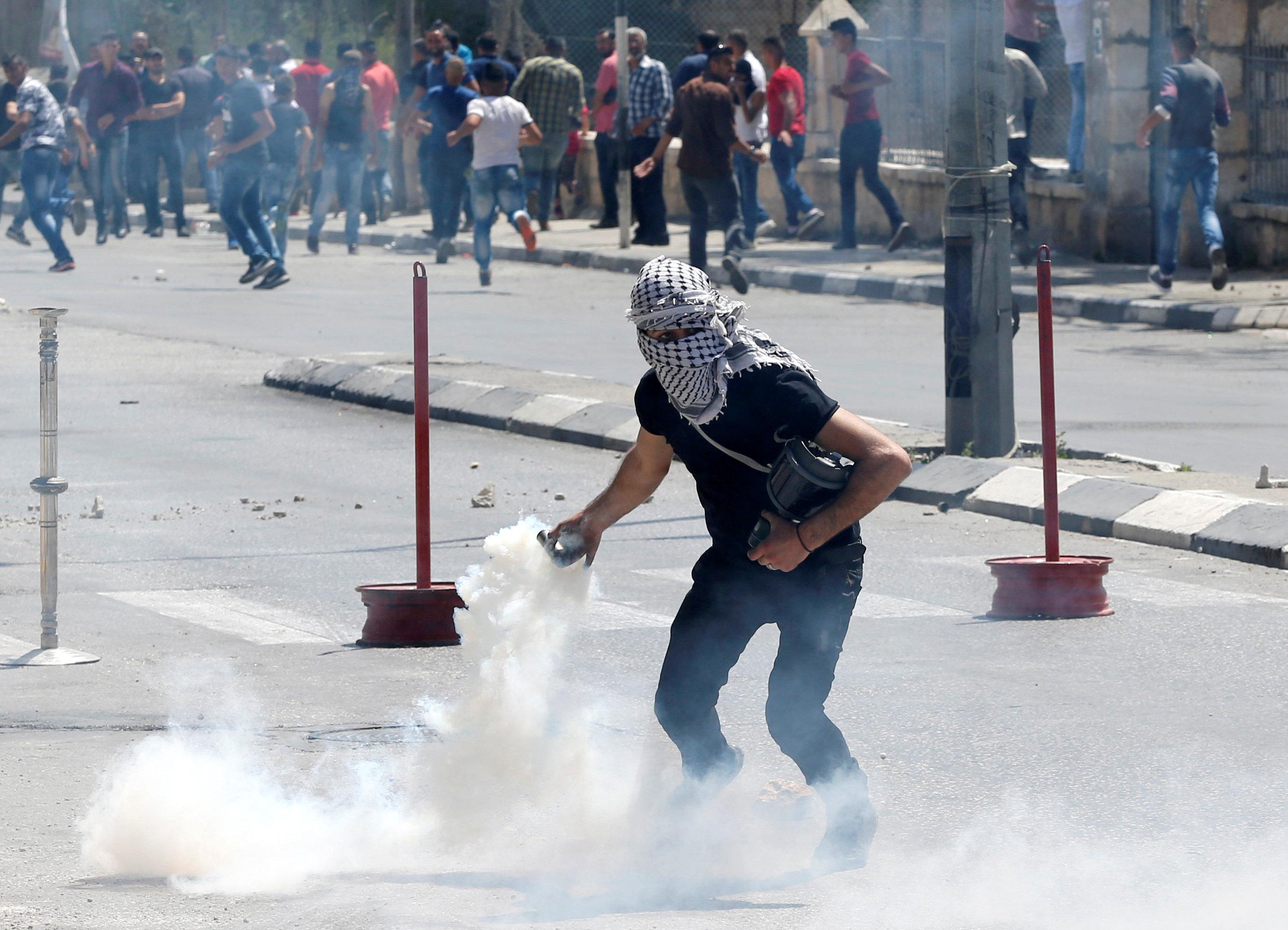 شاب فلسطينى يعيد القاء قنبلة غاز باتجاه قوات الاحتلال