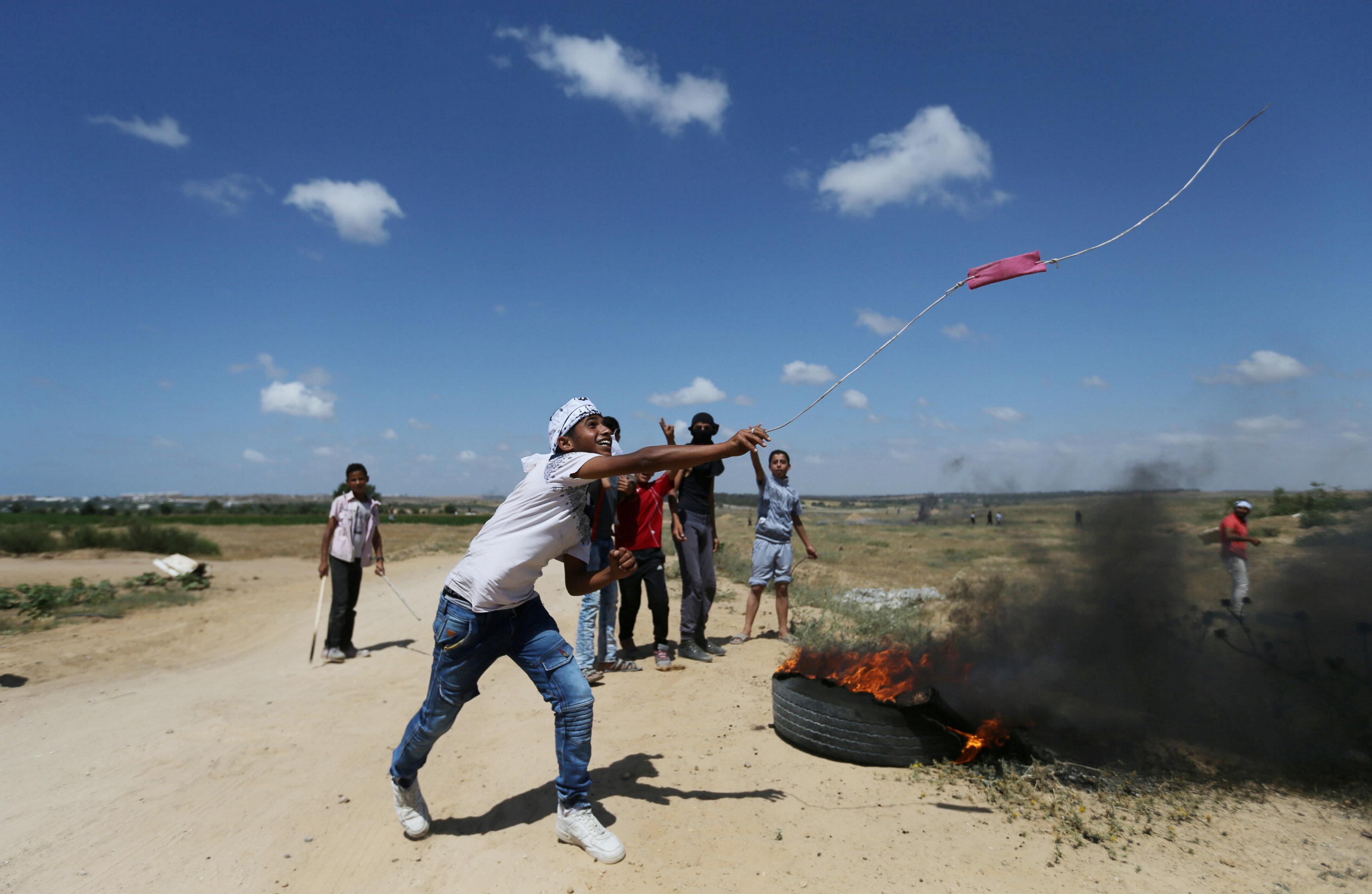 متظاهر فلسطينى يطلق الحجارة على قوات الاحتلال