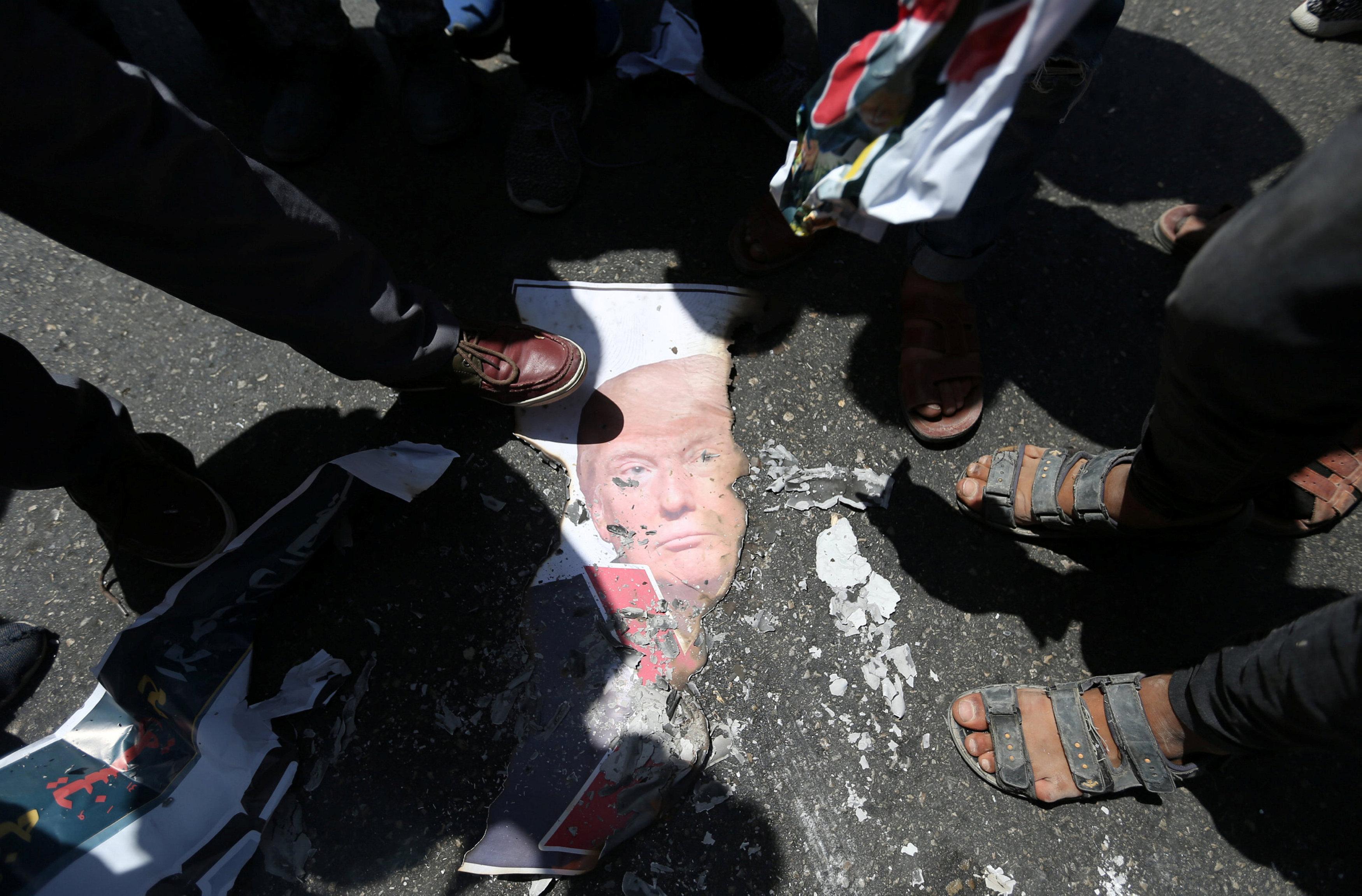 أقدام فلسطنيون علي صورة ترامب