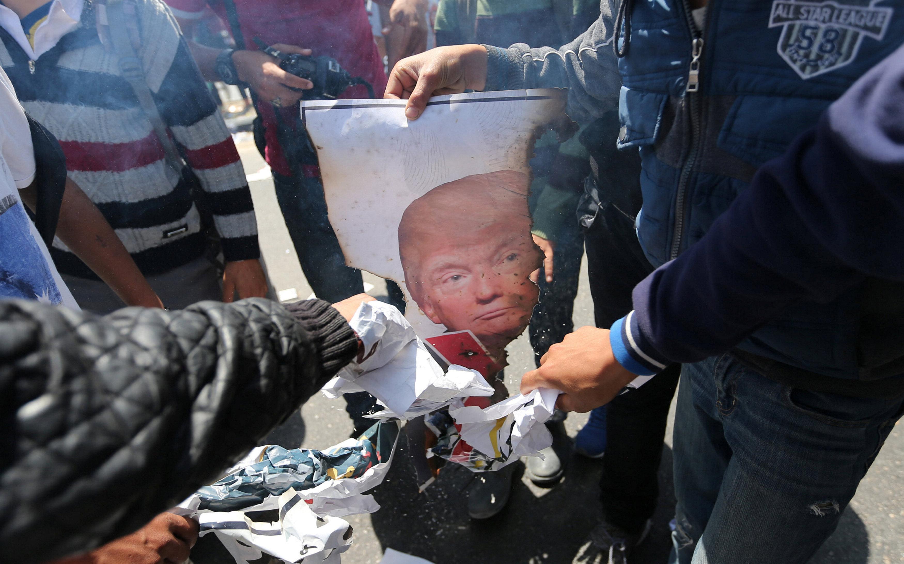 شباب فلسطنييون يحرقون صورة الرئيس الأمريكي