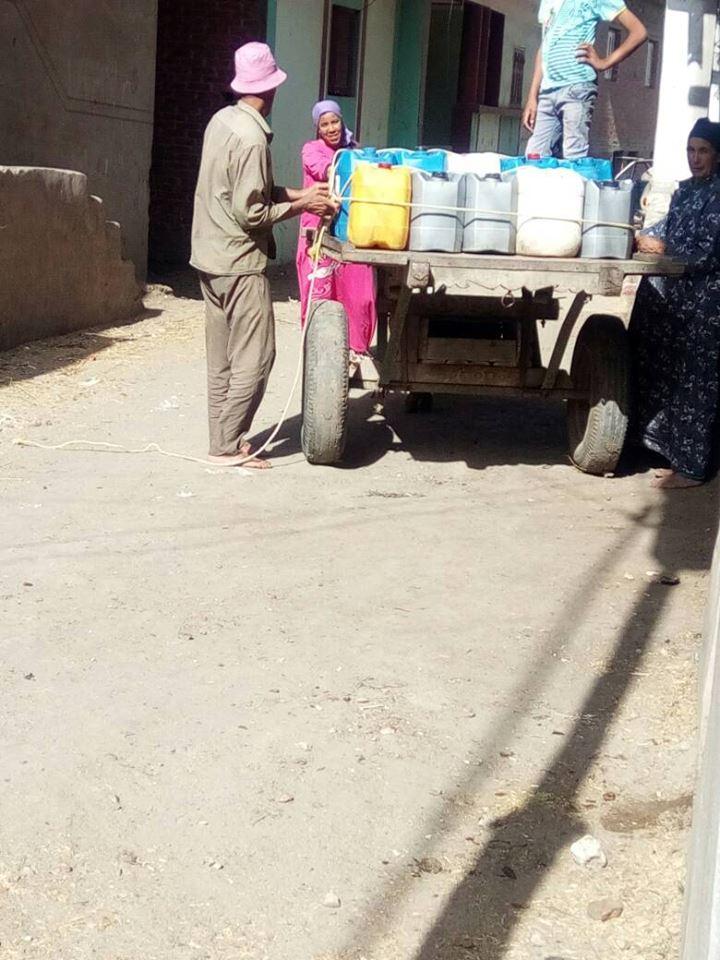 أهالى عزبة غازى يحملون مياه الشرب على العربات
