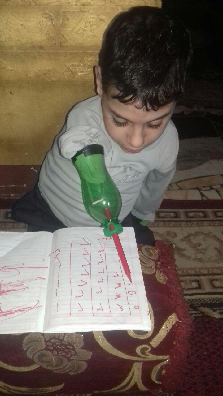 الطفل زياد يكتب مستخدما زجاجة معدنية