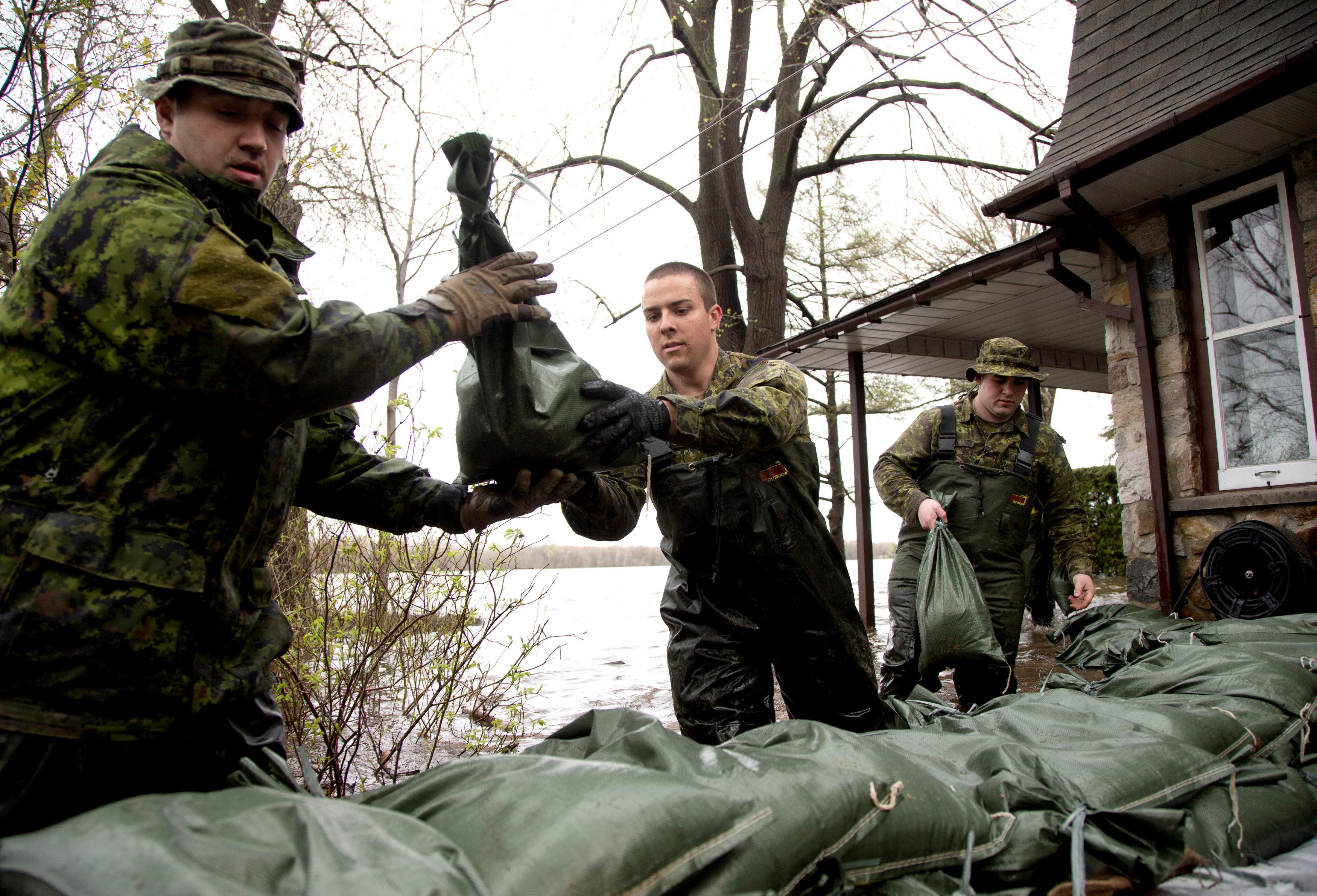 جنود كنديون يضعون أكياس الرمال أمام منزل غمرته المياه