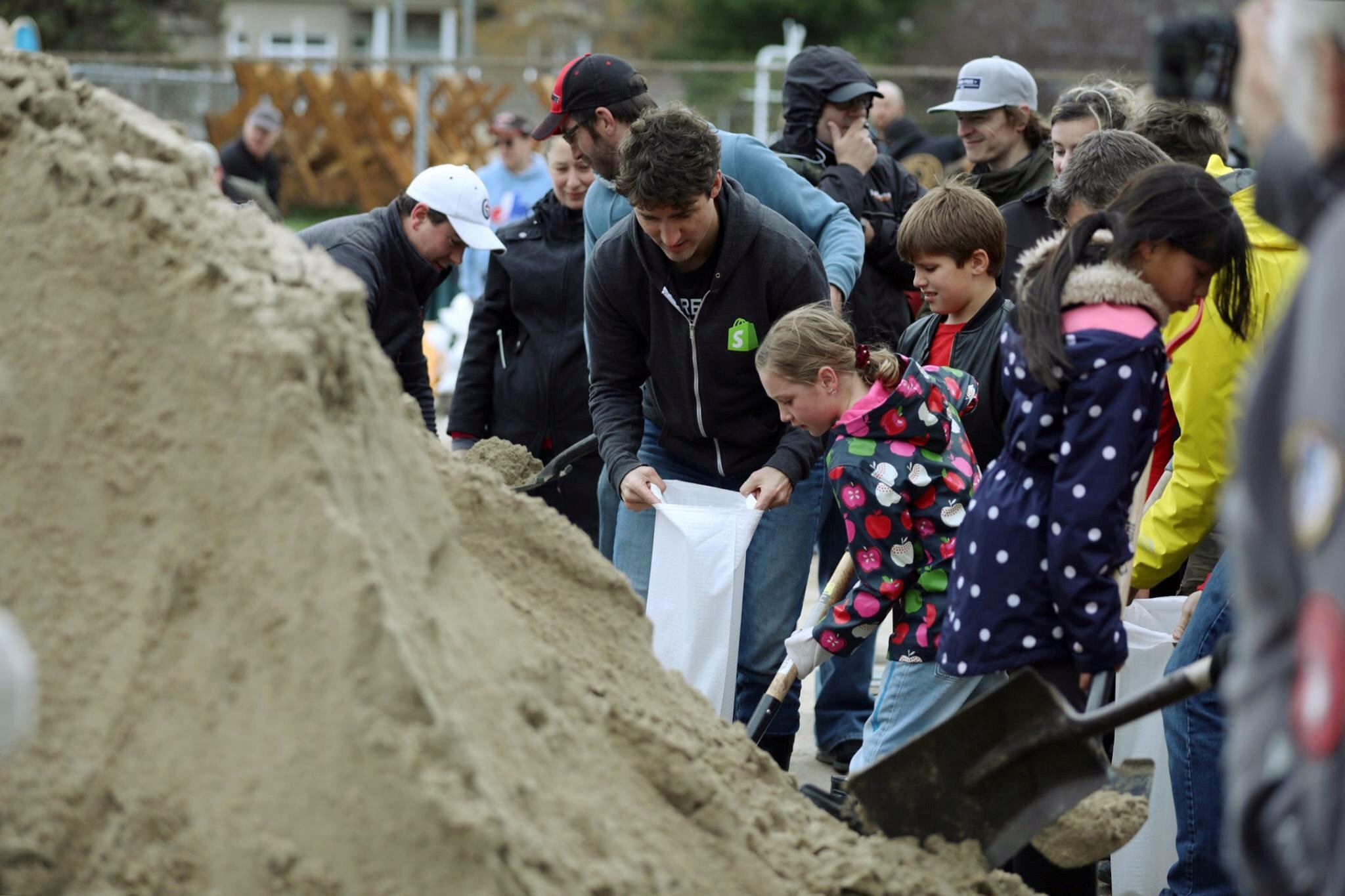 رئيس وزراء كندا يساعد المواطنين فى تعبئة الرمال