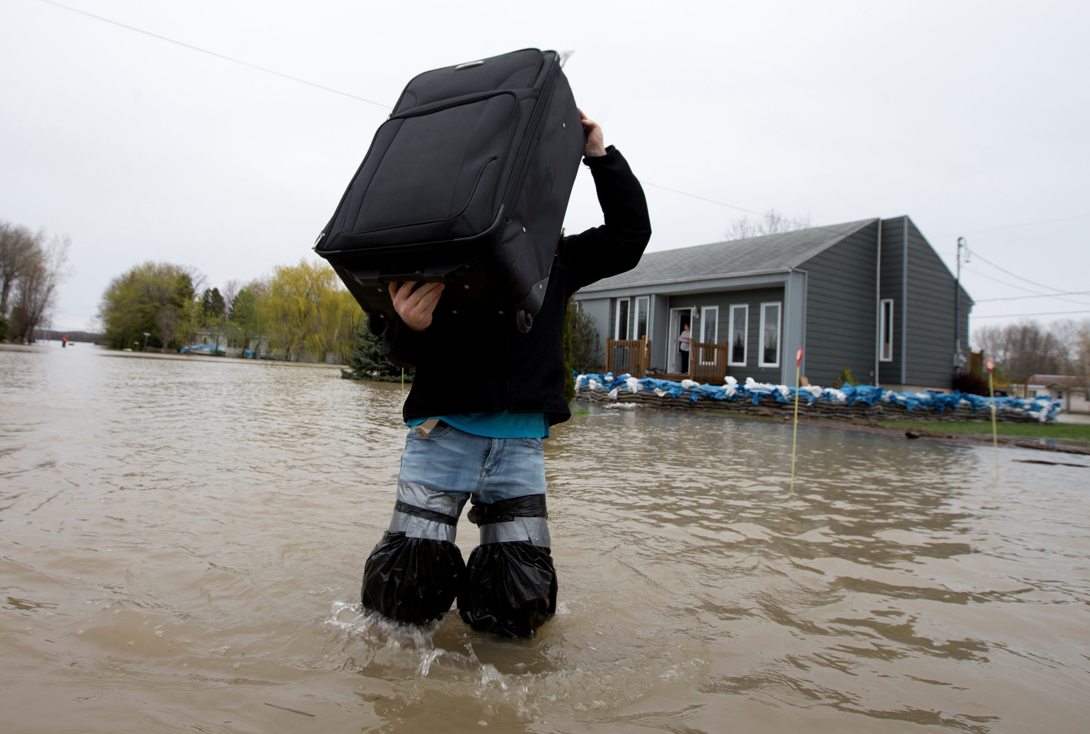 رجل يمشى وسط مياه الفيضانات