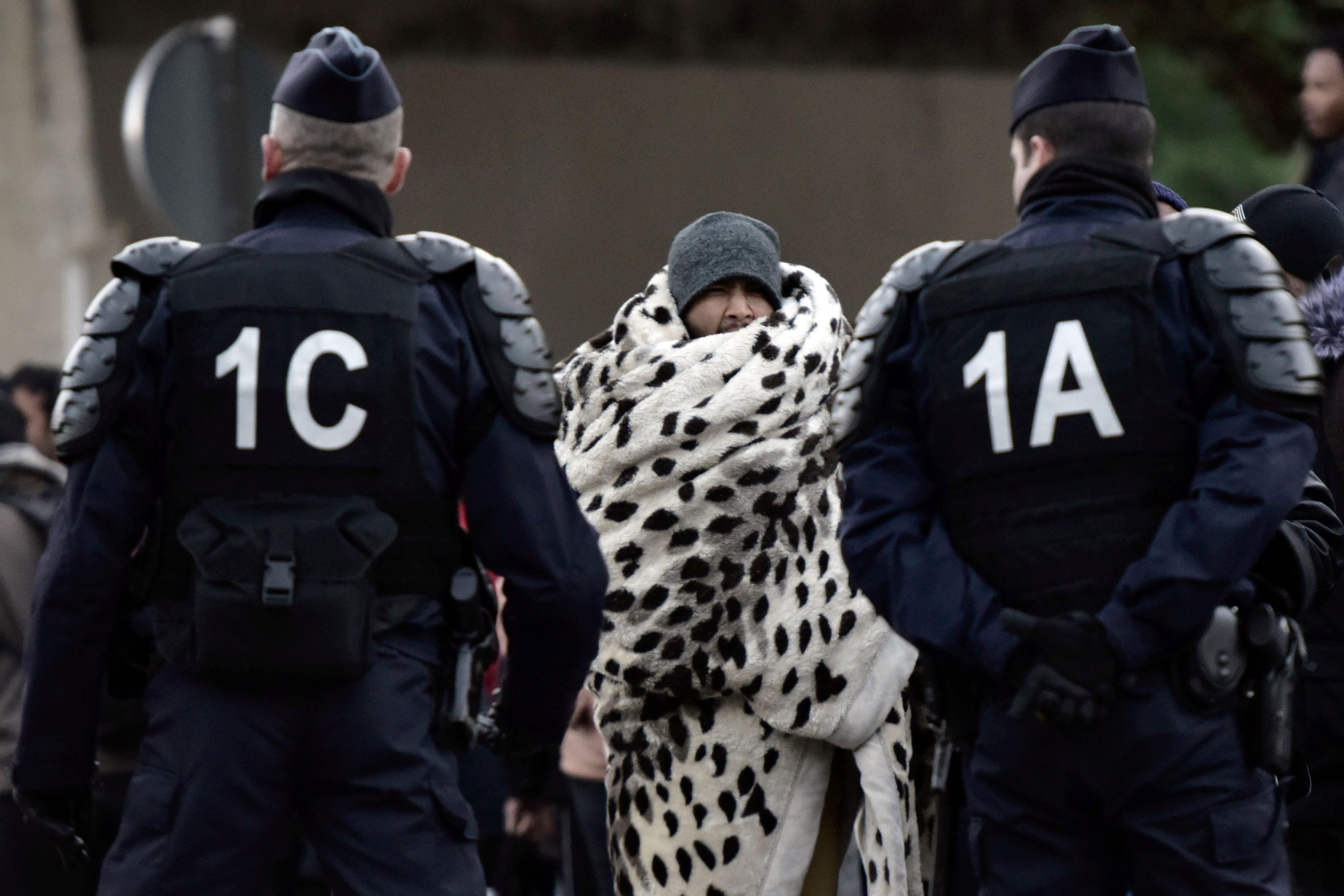 لاجئ يغطى نفسه ببطانية ويقف أمام الشرطة