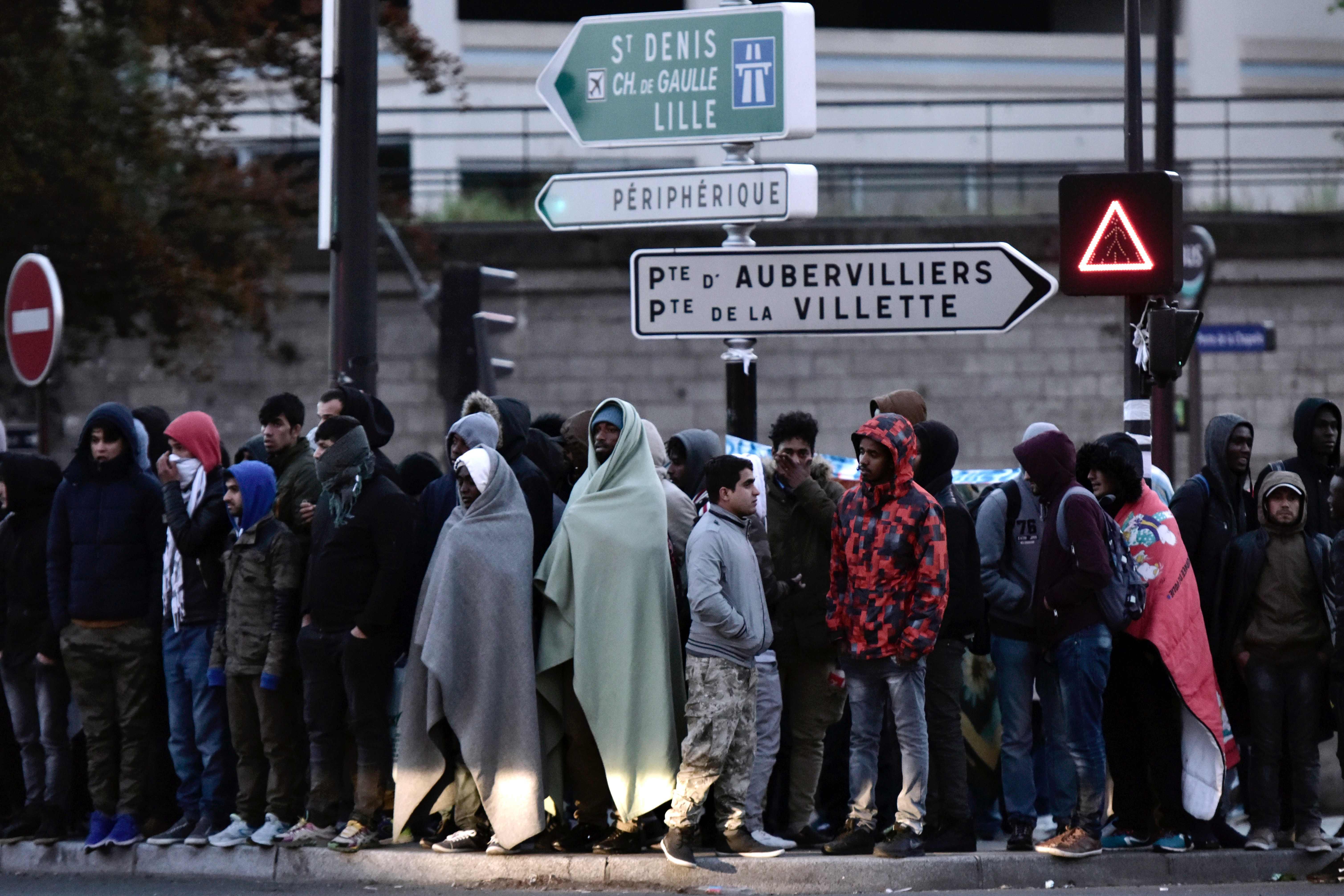اللاجئين يقفون خارج المخيم عقب اخلاؤه