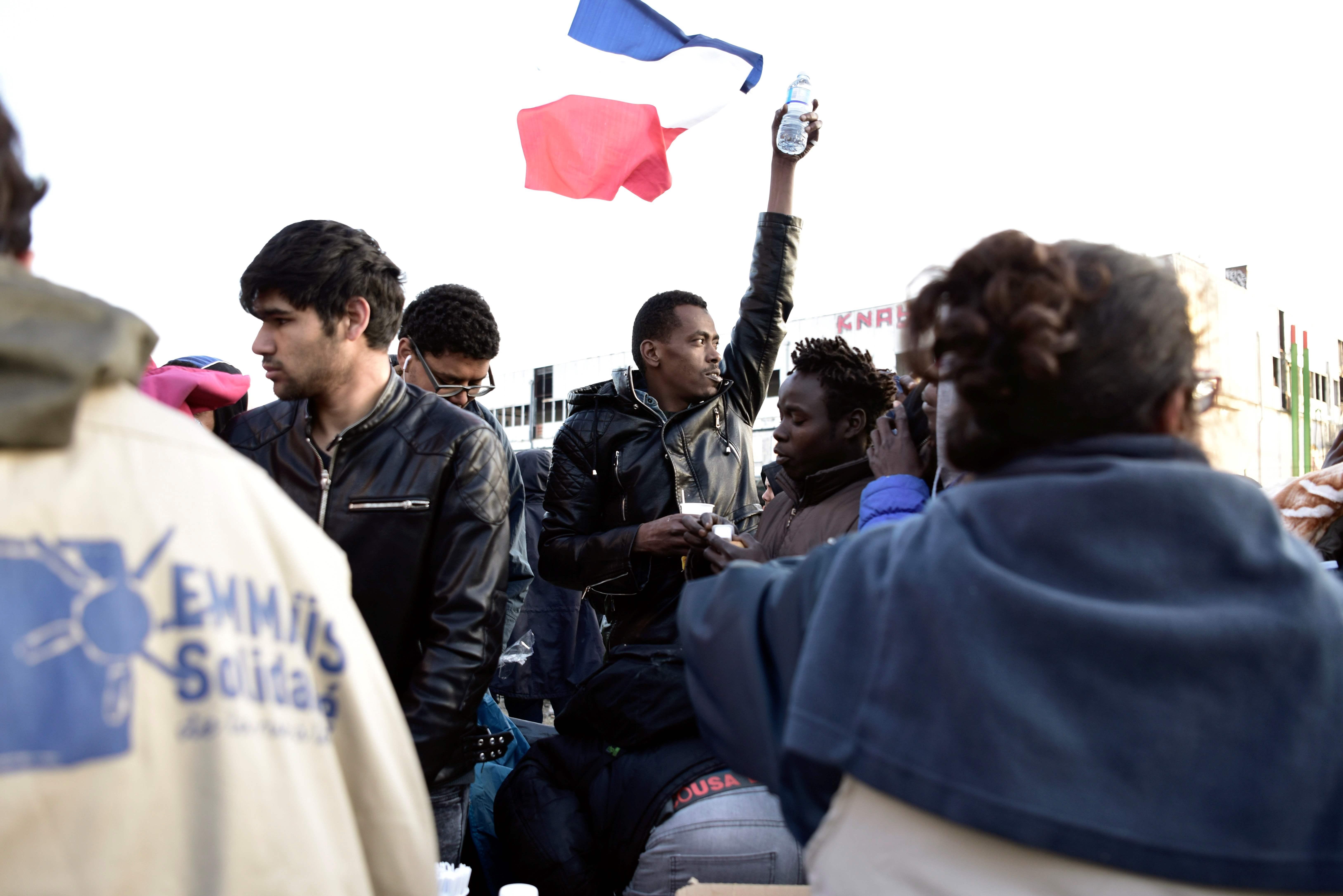 لاجئ يرفع علم فرنسا خلال اخلاء مخيم بباريس