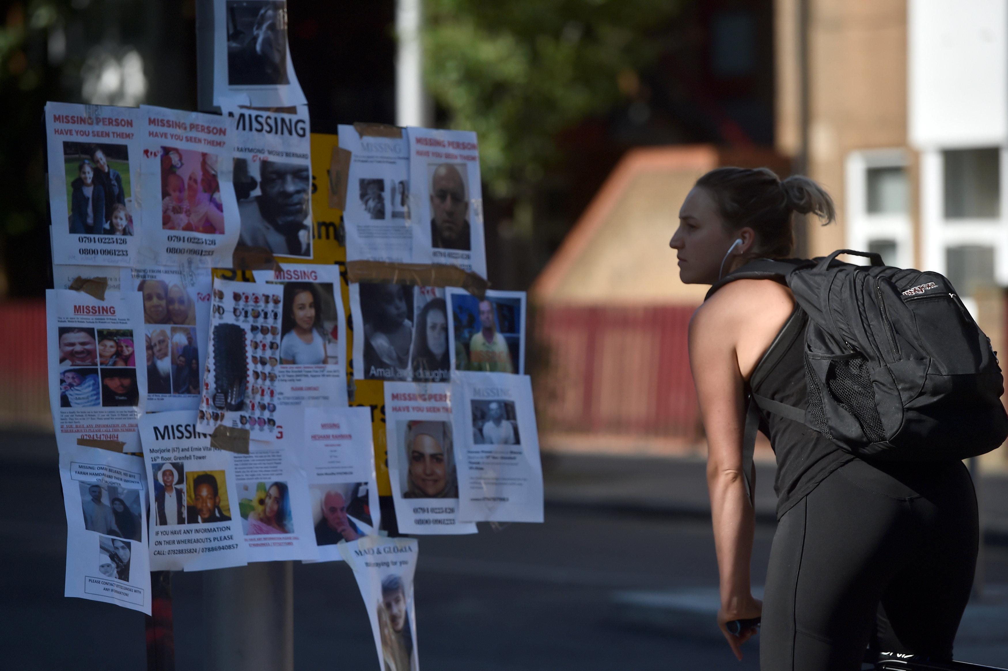 فتاة تتوقف أمام صورضحايا حريق لندن