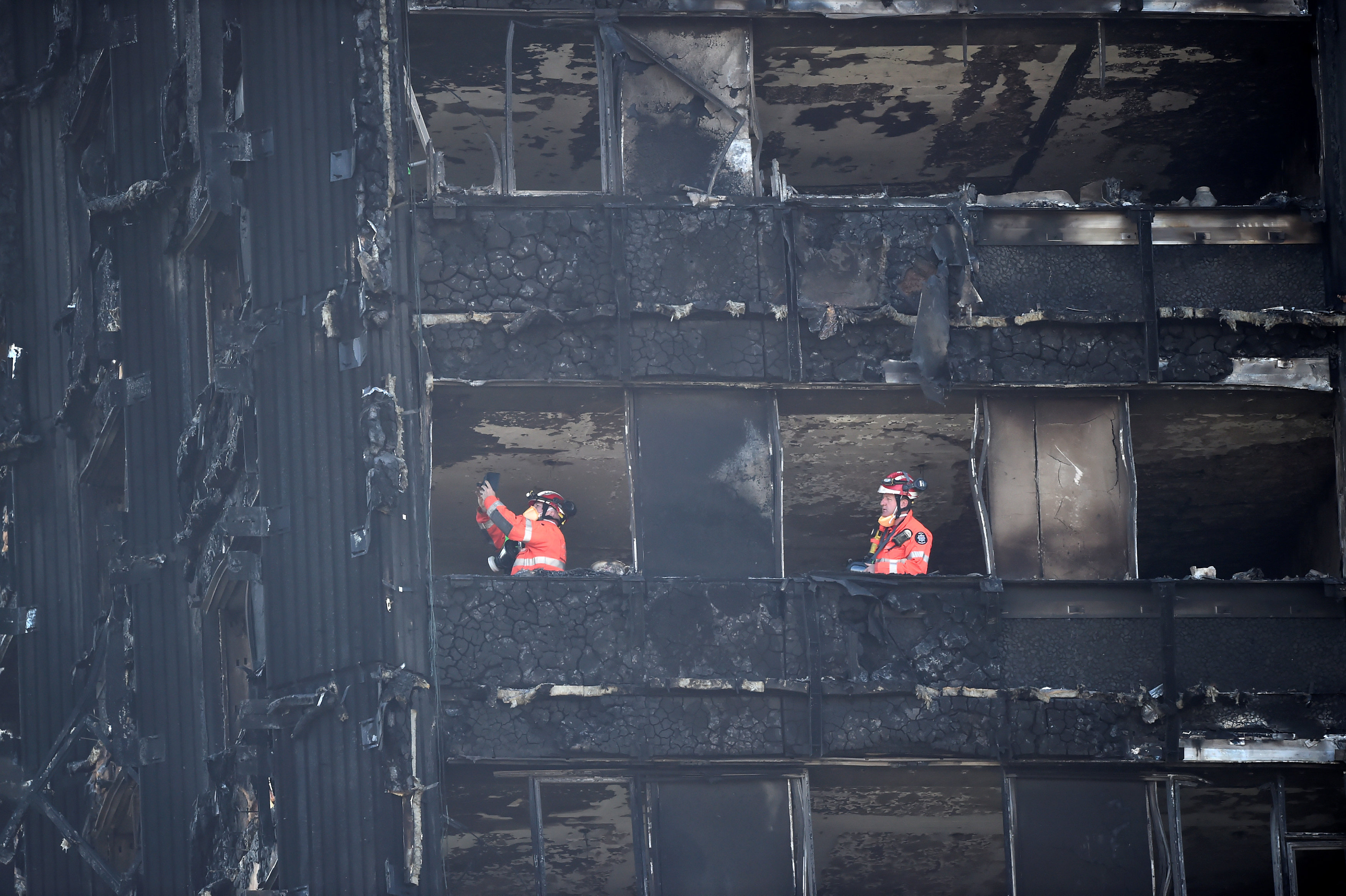 رجال الطوارئ يعاينون البرج المحترق فى لندن