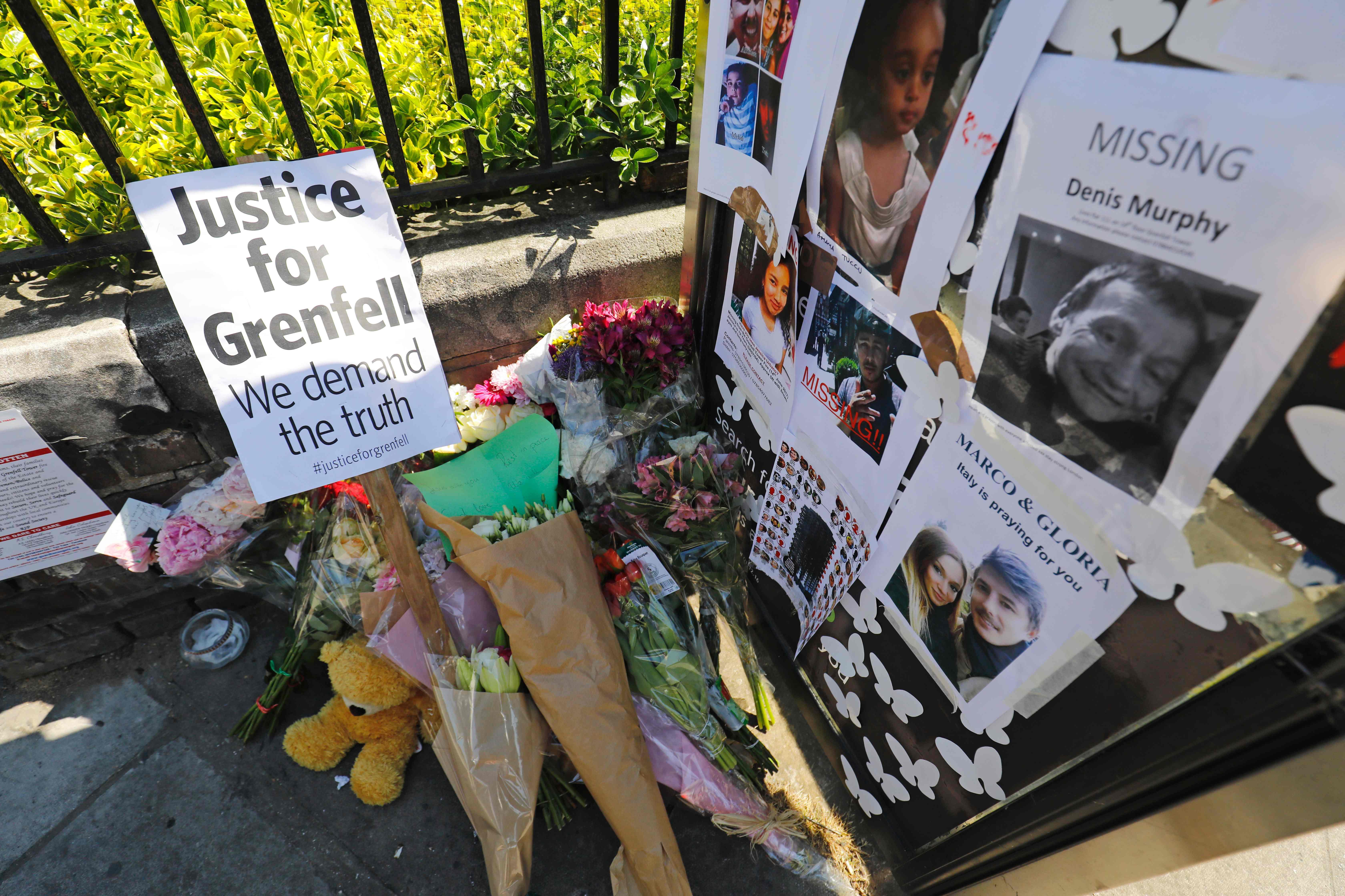 باقات الزهور أمام لافتة تأبين ضحايا الحريق فى لندن