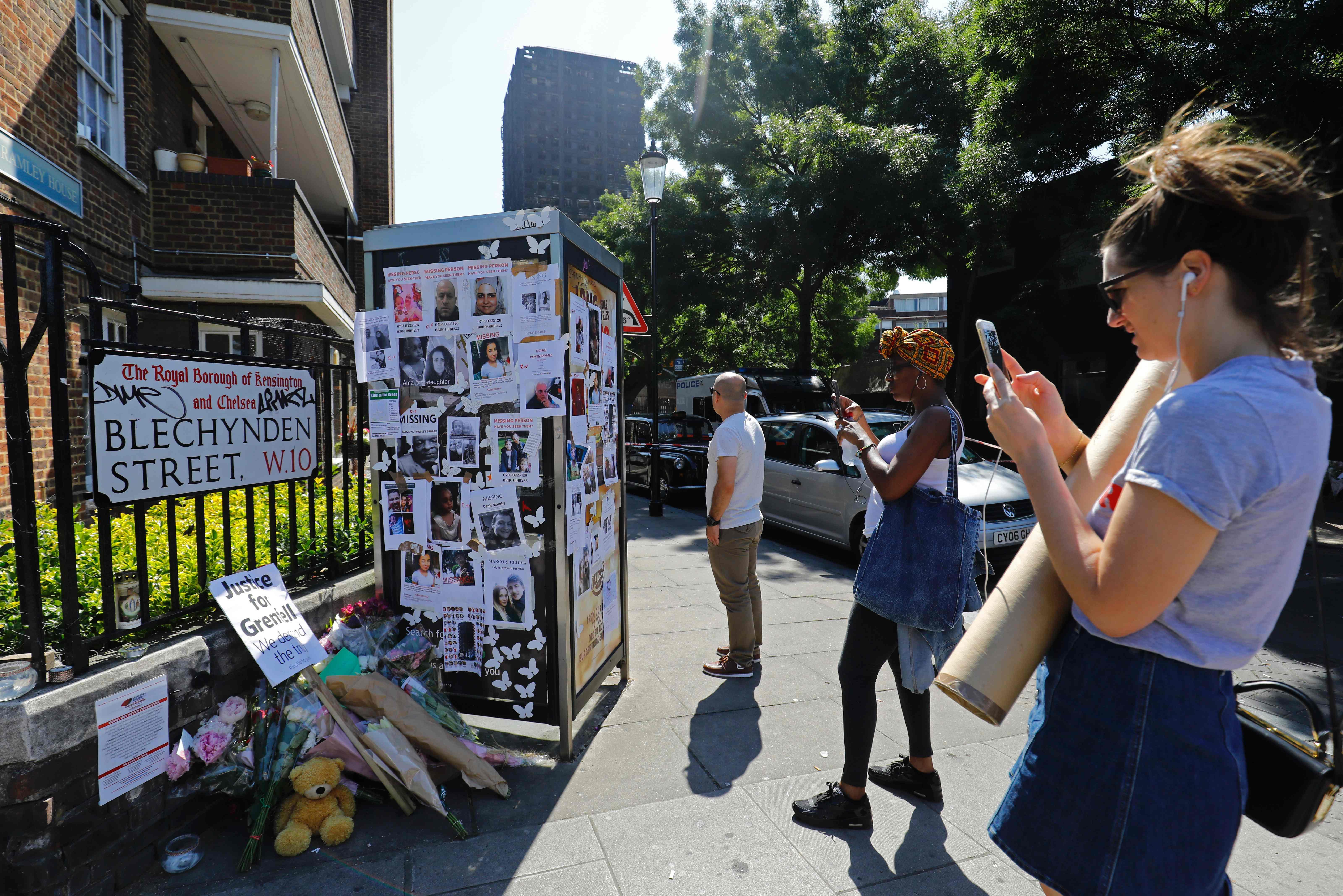 فتاة تصور لافتة تأبين ضحايا حريق لندن