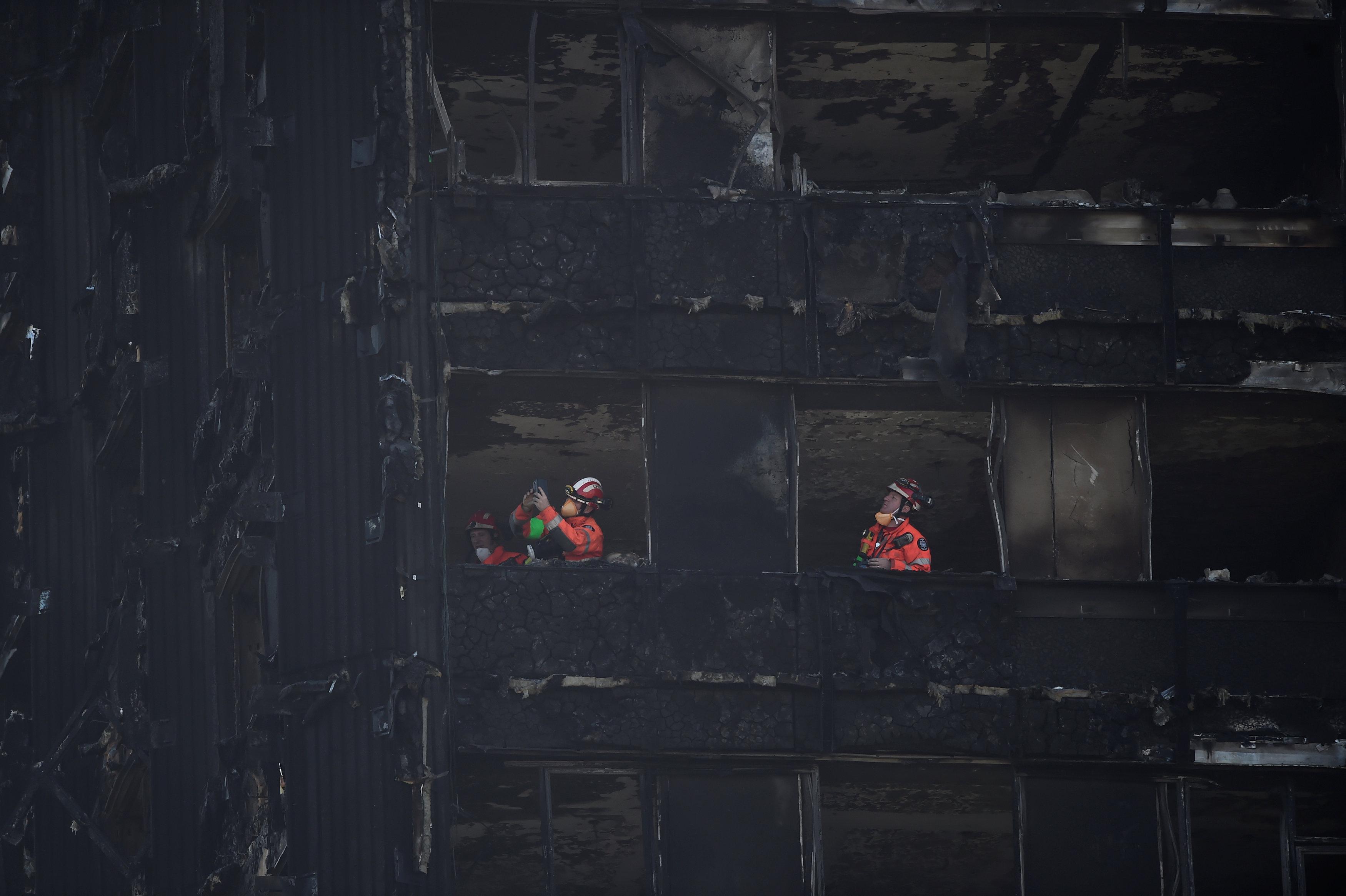 رجال الطوارئ يواصلون عملهم فى البرج المحترق