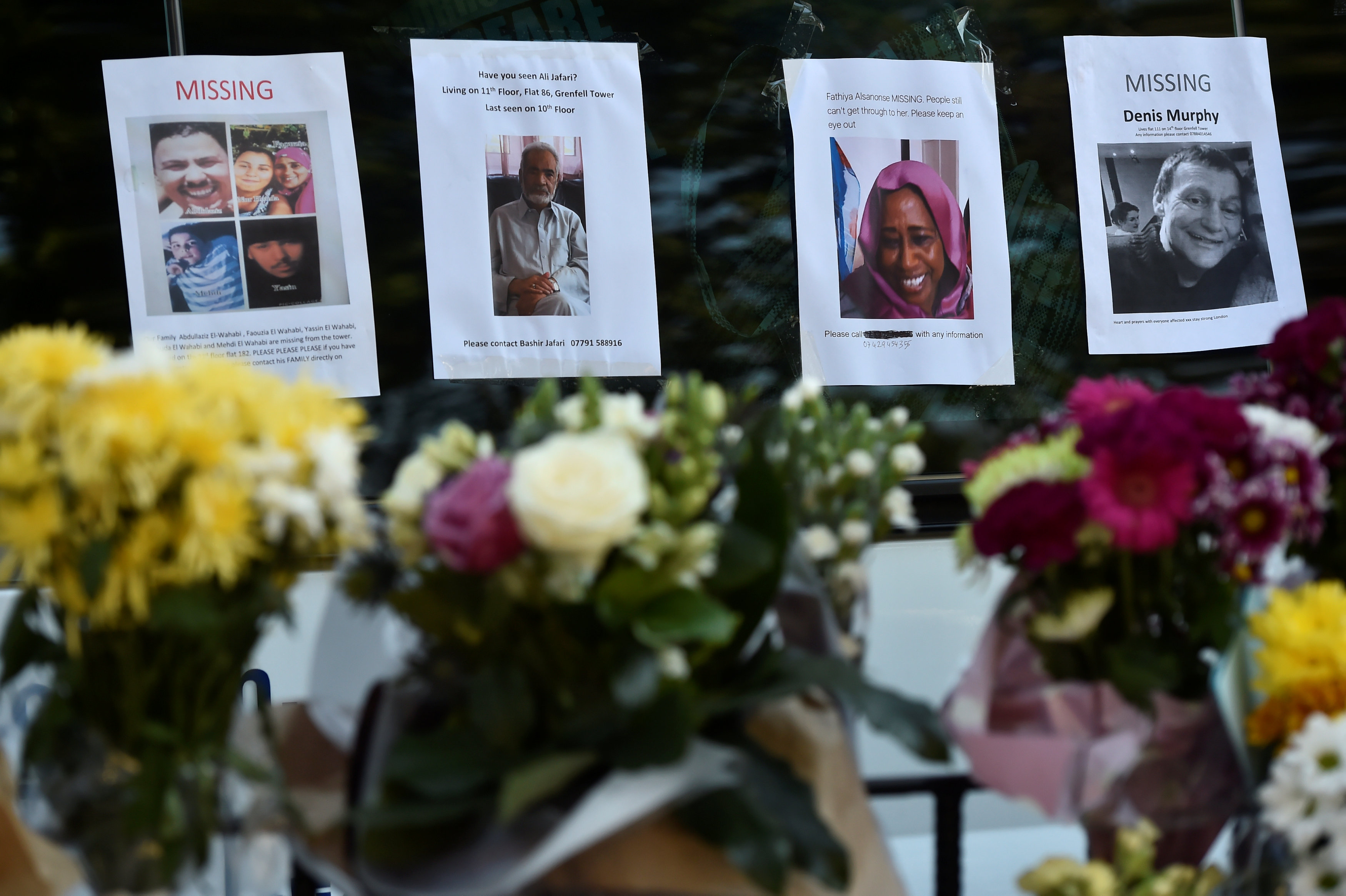 باقات زهور أمام صور ضحايا حريق لندن